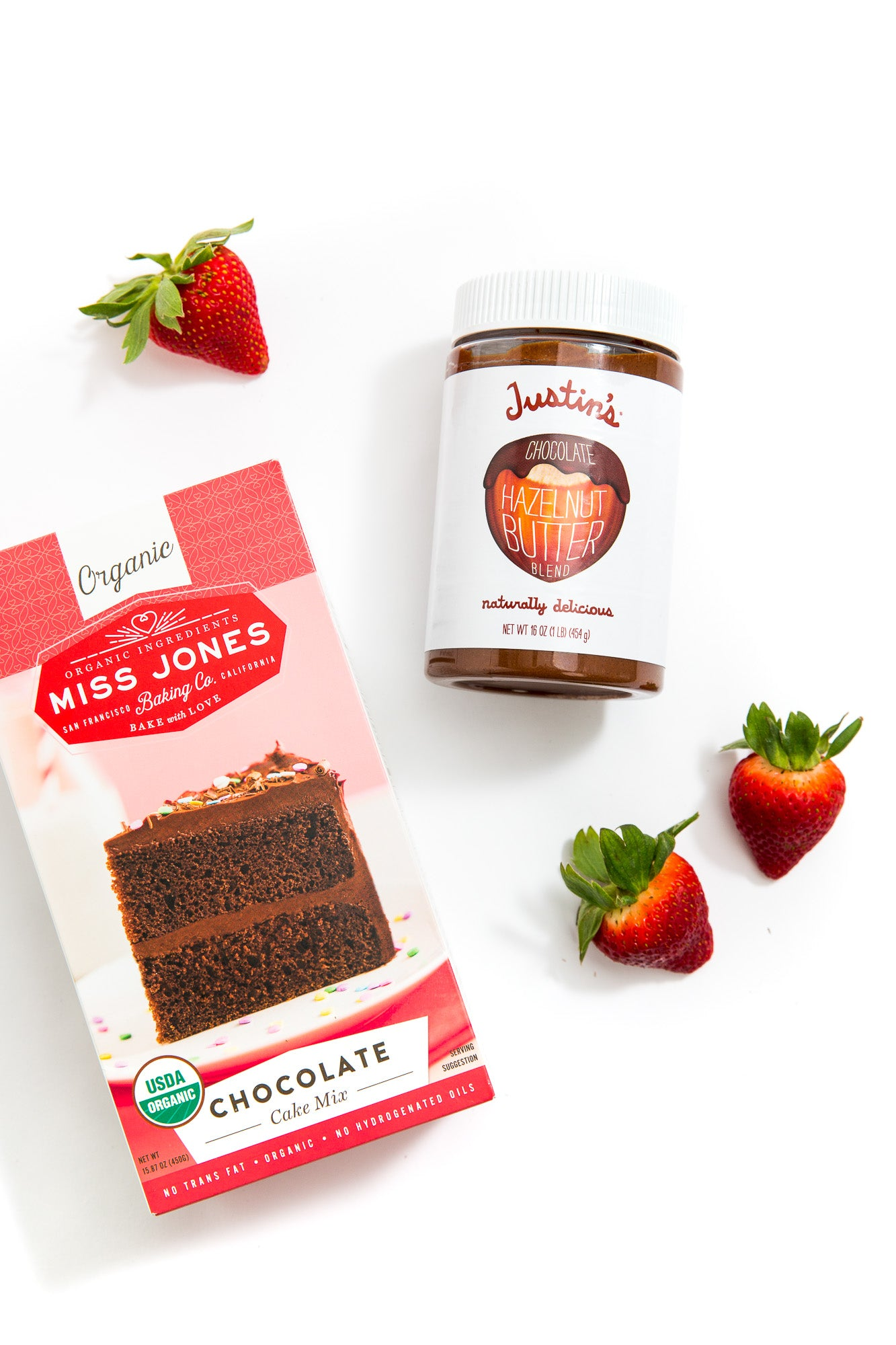 Top view of Miss Jones Baking Organic Chocolate Cake Mix, a couple of strawberries and a tub of Justin's Chocolate Hazelnut butter used for Miss Jones Baking Co Chocolate Hazelnut Strawberry Cupcakes recipe