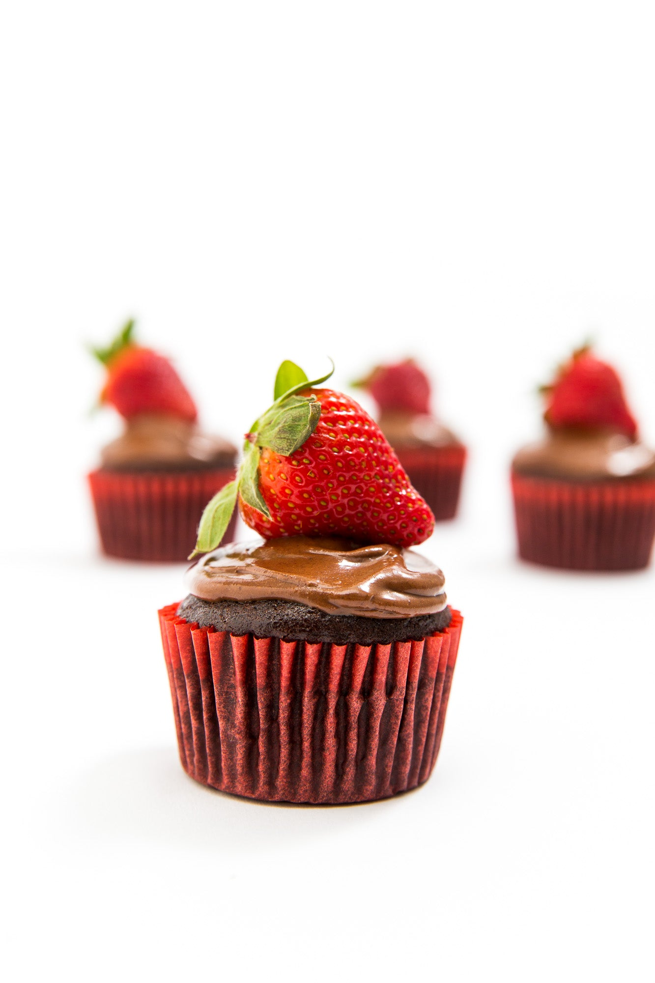 A close up of one Miss Jones Baking Co Chocolate Hazelnut Strawberry Cupcakes in front of three other Miss Jones Baking Co Chocolate Hazelnut Strawberry Cupcakes