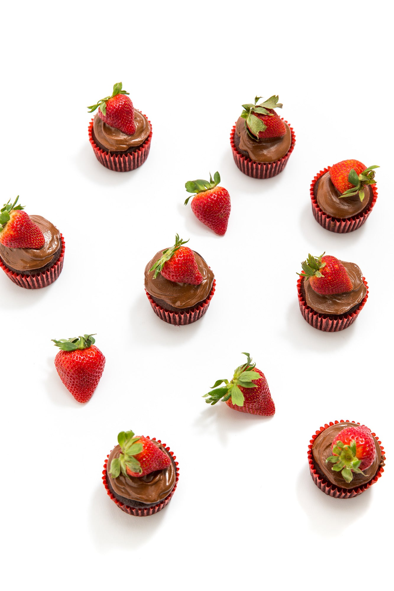 Image from above of eight Miss Jones Baking Co Chocolate Hazelnut Strawberry Cupcakes scattered around a couple of strawberries