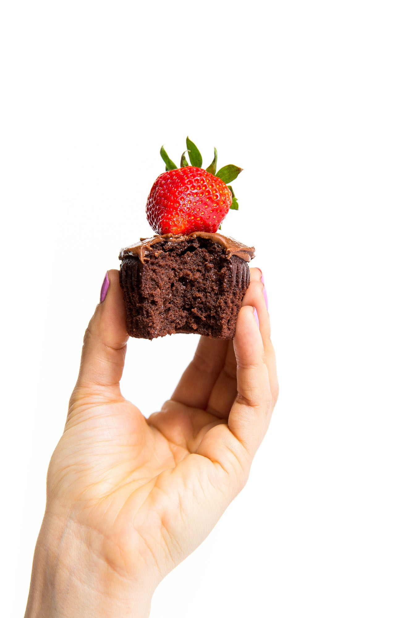 A hand holding a half eaten Miss Jones Baking Co Chocolate Hazelnut cupcake with a strawberry on top