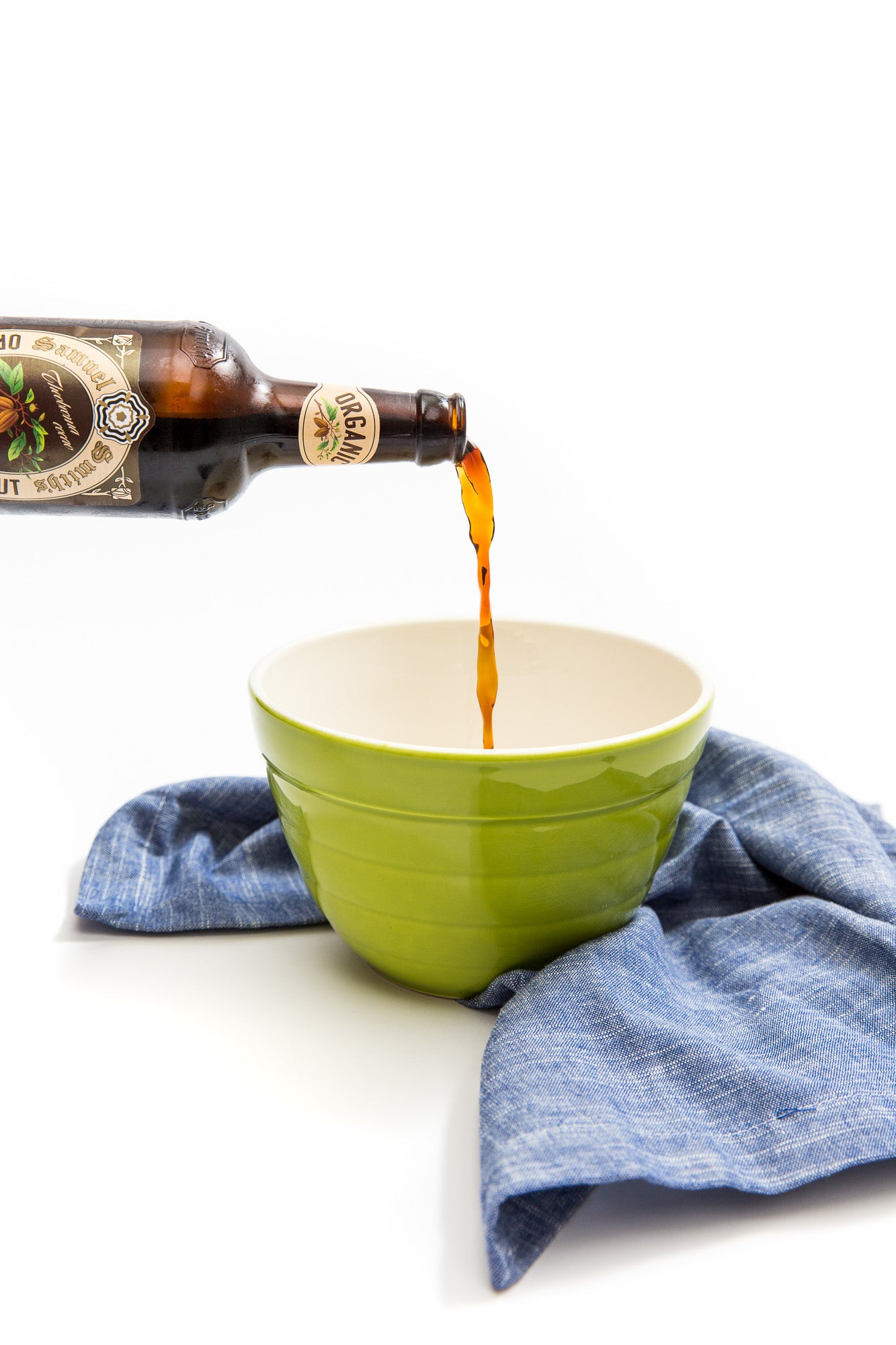 Image of a bottle of stout being poured into a green bowl next to a blue towel for Miss Jones Baking Co Double Chocolate Stout Pancakes Recipe