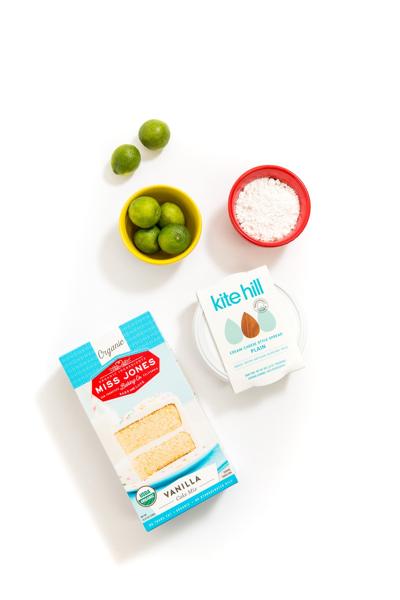 Image from above of a box of Miss Jones Vanilla Cake mix next to a bowl of limes and a tub of Kite Hill Cream Cheese Spread for Miss Jones Baking Co Key Lime Margarita Bars Recipe