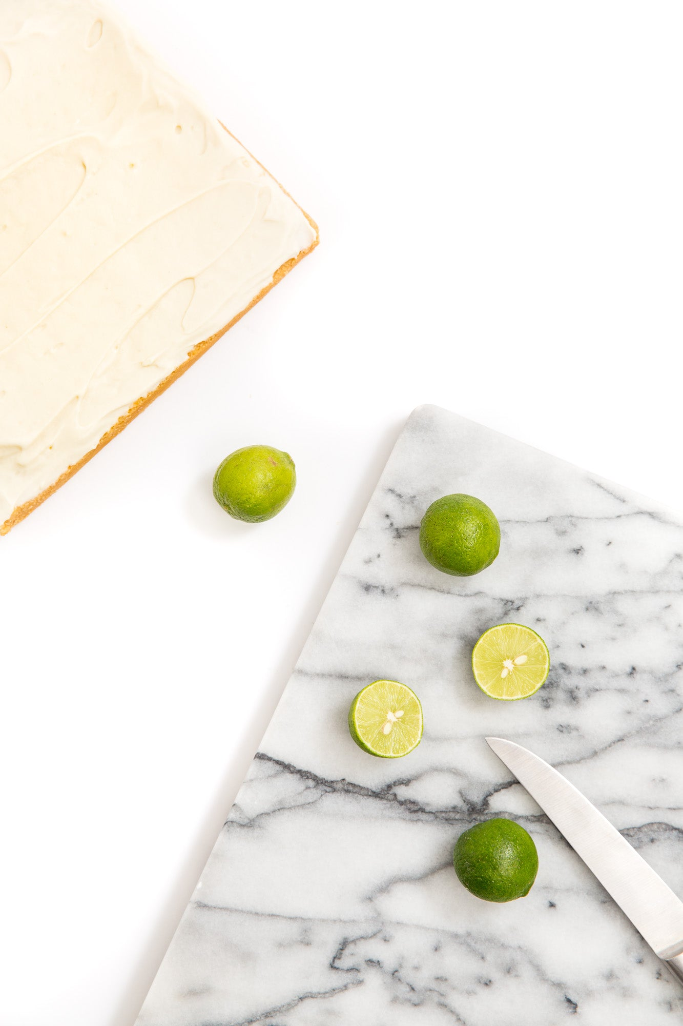 Image of part of Miss Jones Baking Co Key Lime Margarita Bars next to a marble cutting board with limes and a knife