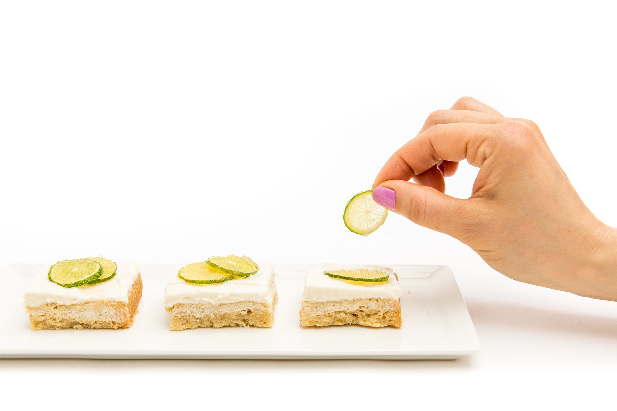 Image from the side of a hand putting baked lime slices on three Miss Jones Baking Co Key Lime Margarita Bars on a plate