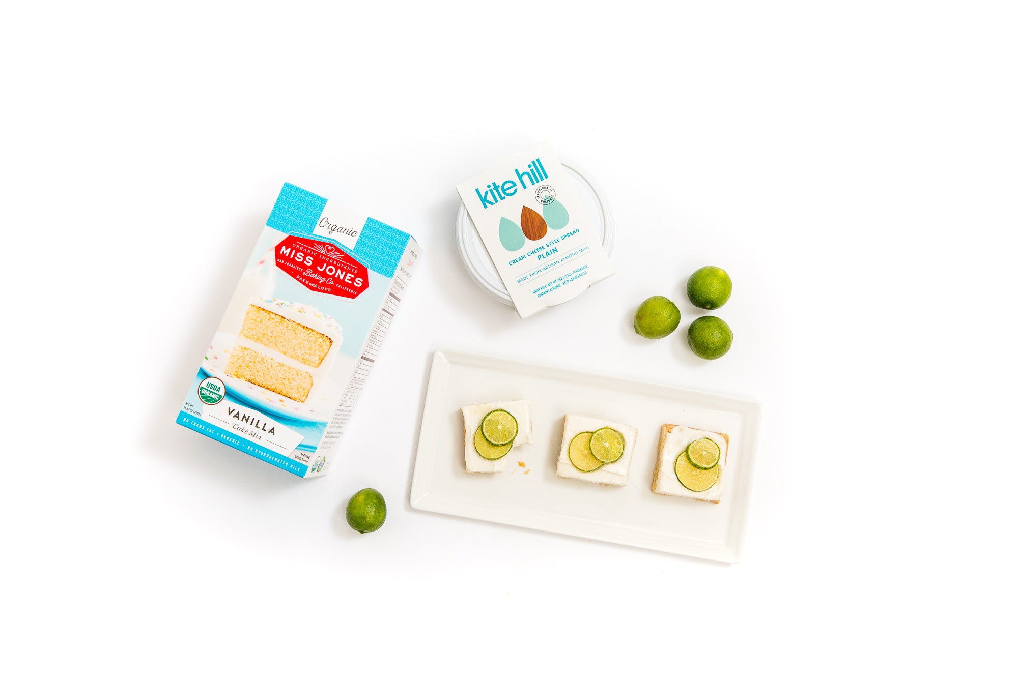 Image from above of a plate with three Miss Jones Baking Co Key Lime Margarita Bars, four limes, a box of Miss Jones Vanilla Cake Mix and a tub of Kite Hill Cream Cheese spread