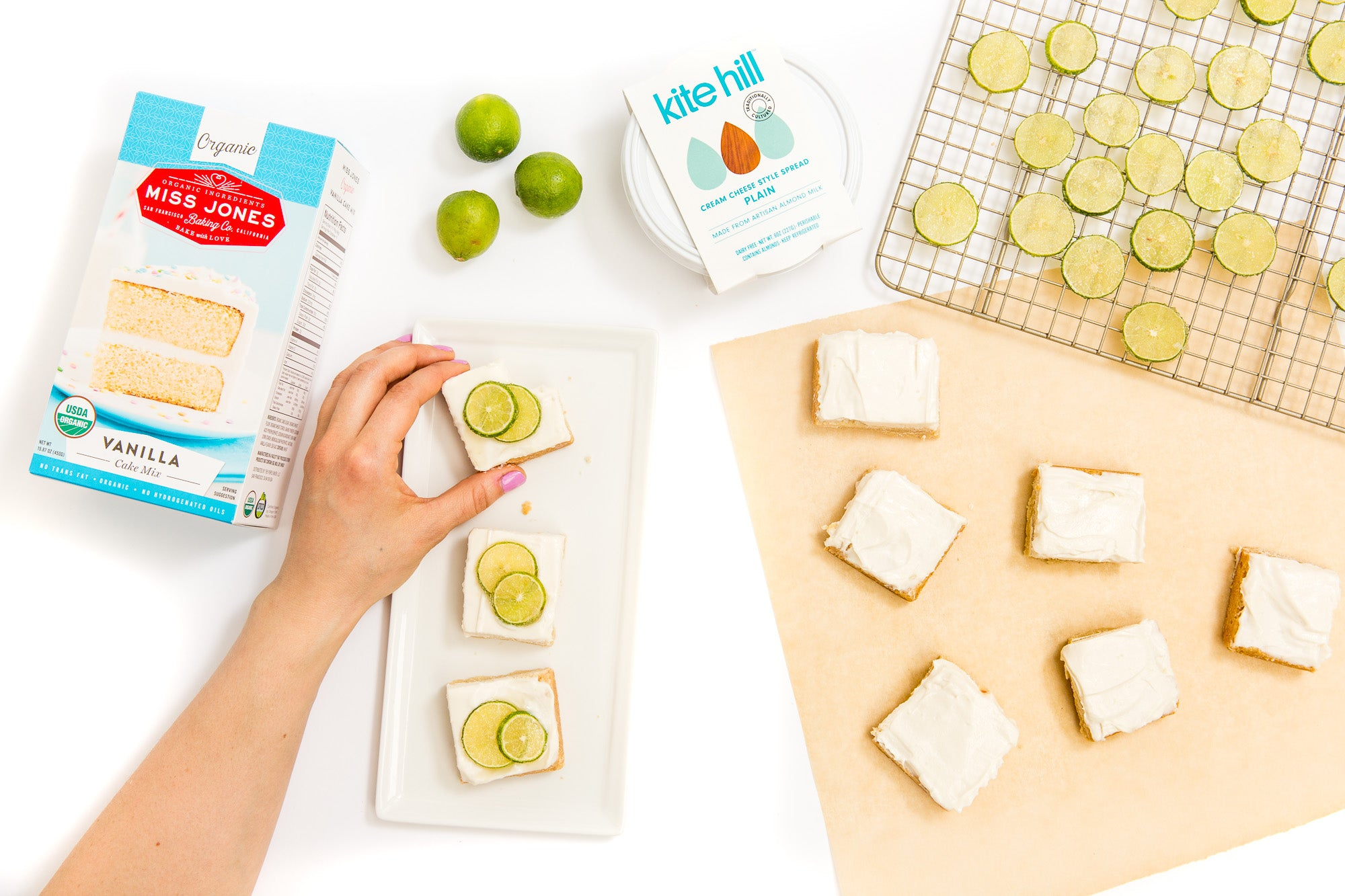 Image of a hand taking a Miss Jones Baking Co Key Lime Margarita Bar off of a plate next to a box of Miss Jones Vanilla Cake Mix, three limes, a tub of Kite Hill Cream Cheese spread, lime slices on a baking rack and six unfinished Miss Jones Baking Co Key Lime Margarita Bars
