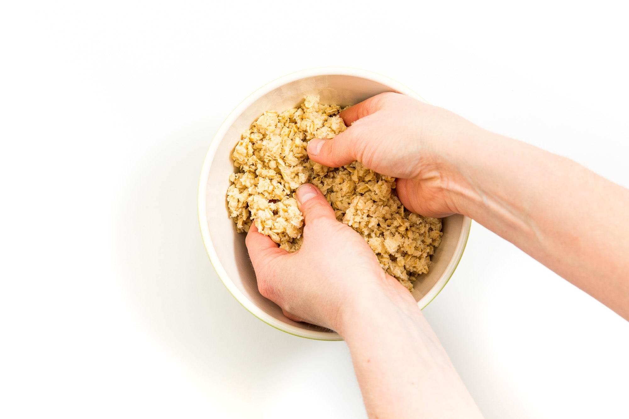 Image from above of hands mixing dough in a bowl for Miss Jones Baking Co Mini Berry Crumbles recipe