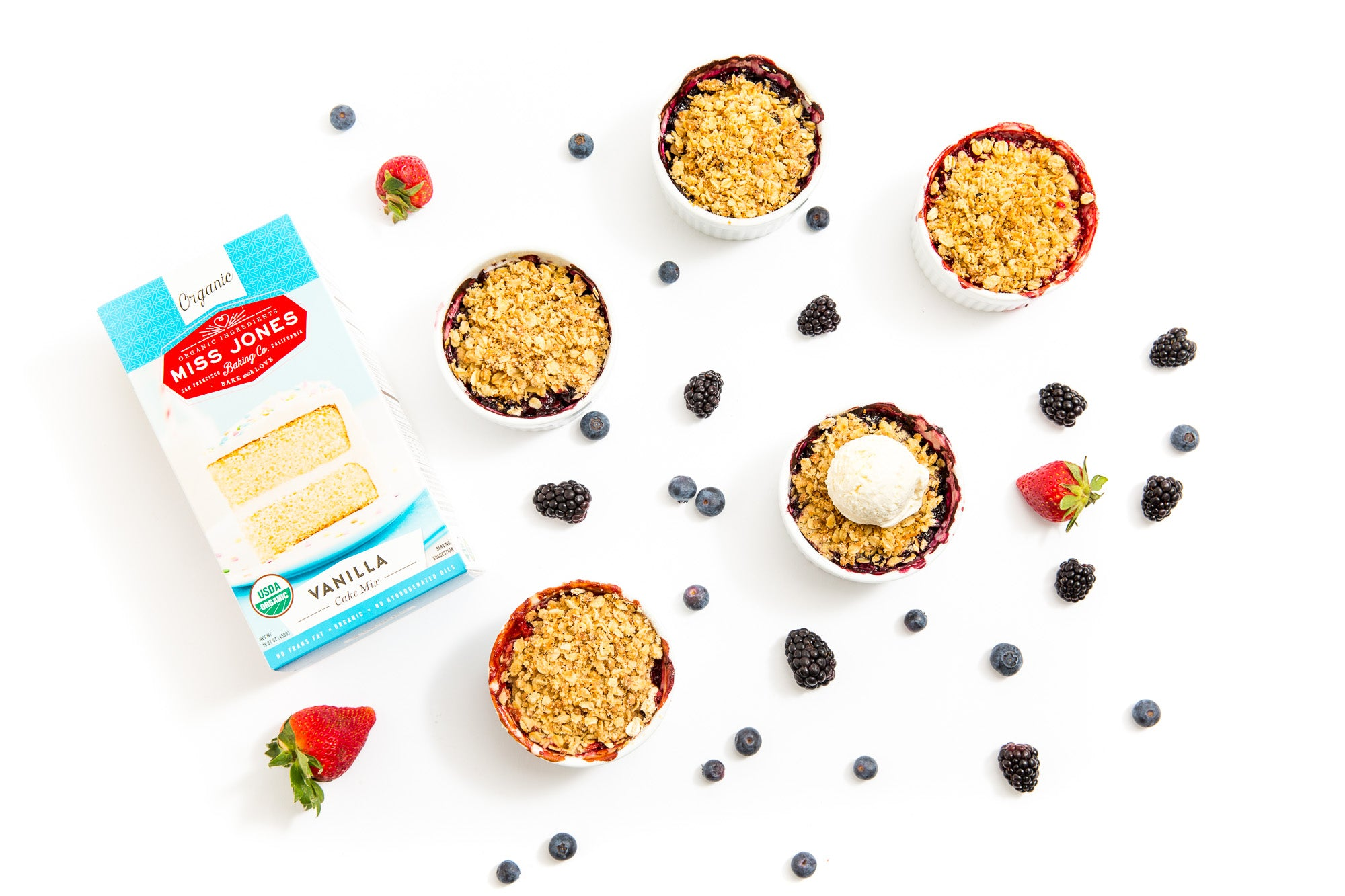 Image from above of four Miss Jones Baking Co Mini Berry Crumbles next to a box of Miss Jones Vanilla Cake Mix surrounded by blackberries, blueberries, and a strawberry