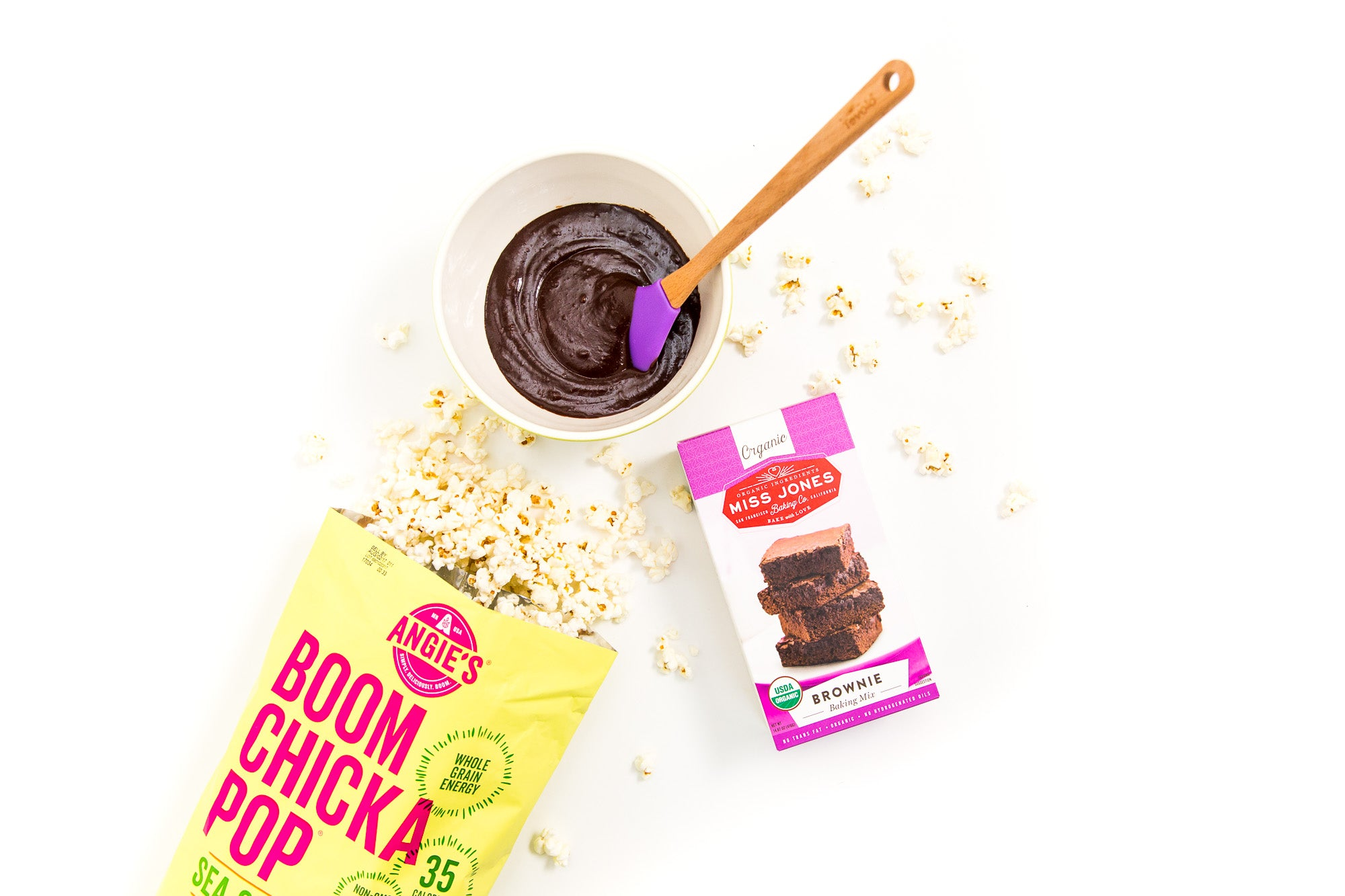 Image from above of a box of Miss Jones Brownie Mix next to a bag of Boom Chicka Pop Sea Salt Popcorn and a bowl of chocolate for Miss Jones Baking Co Popcorn Brownies Recipe