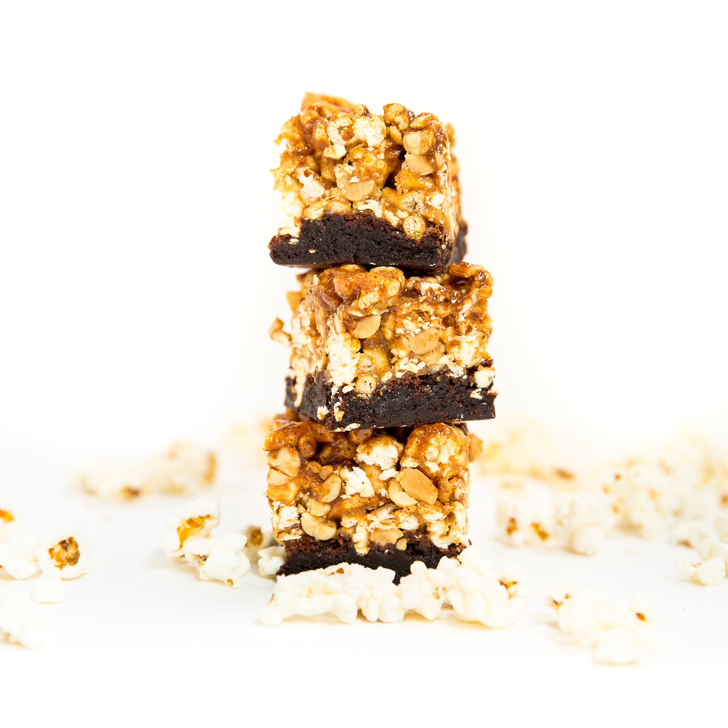 Image of three Miss Jones Baking Co Popcorn Brownies stacked and surrounded by popcorn