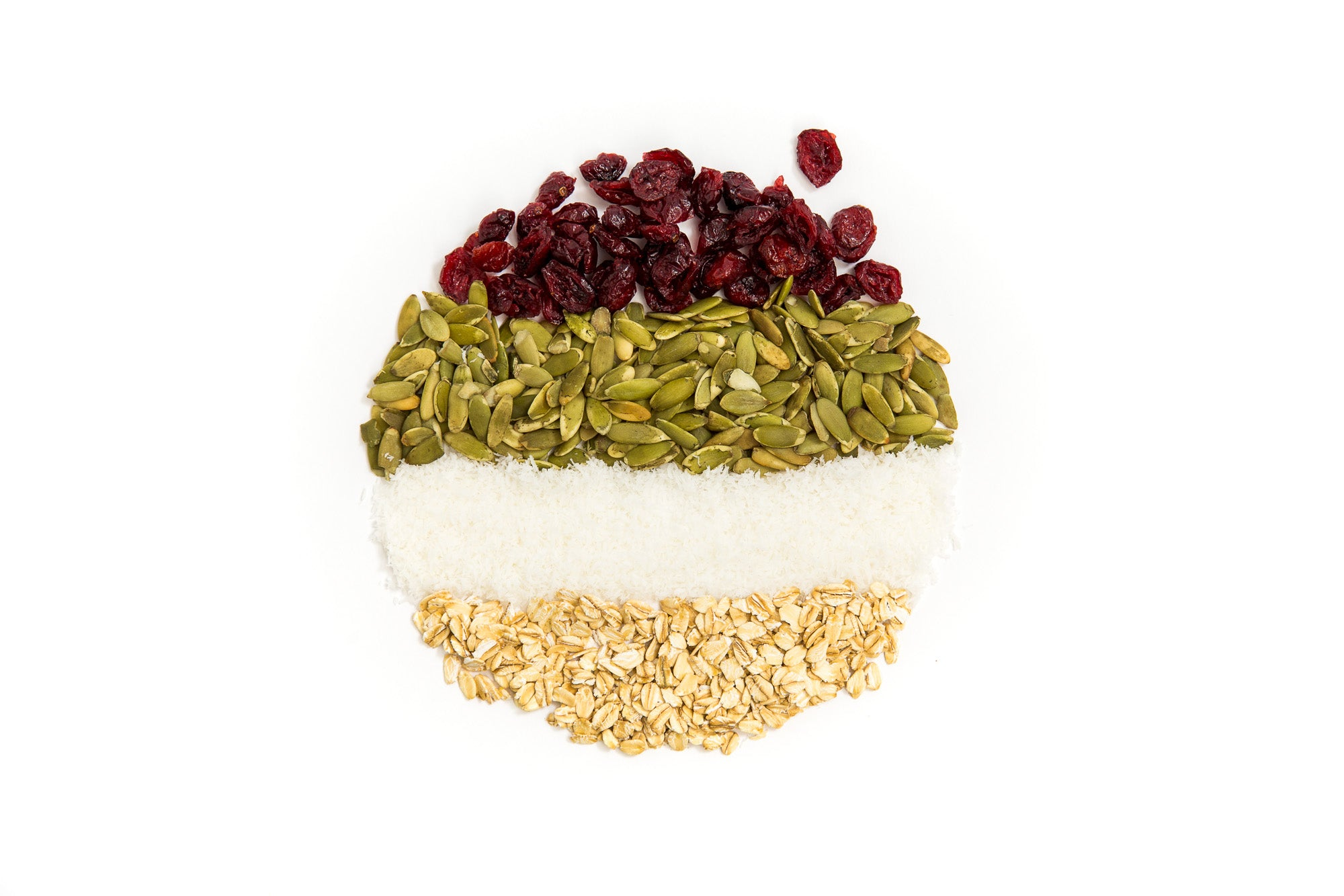 Image of cranberries, pumpkin seeds, coconut flakes and oats placed in lines to form a circle used for Miss Jones Baking Co Happy Trails Mix Cookie Bites recipe
