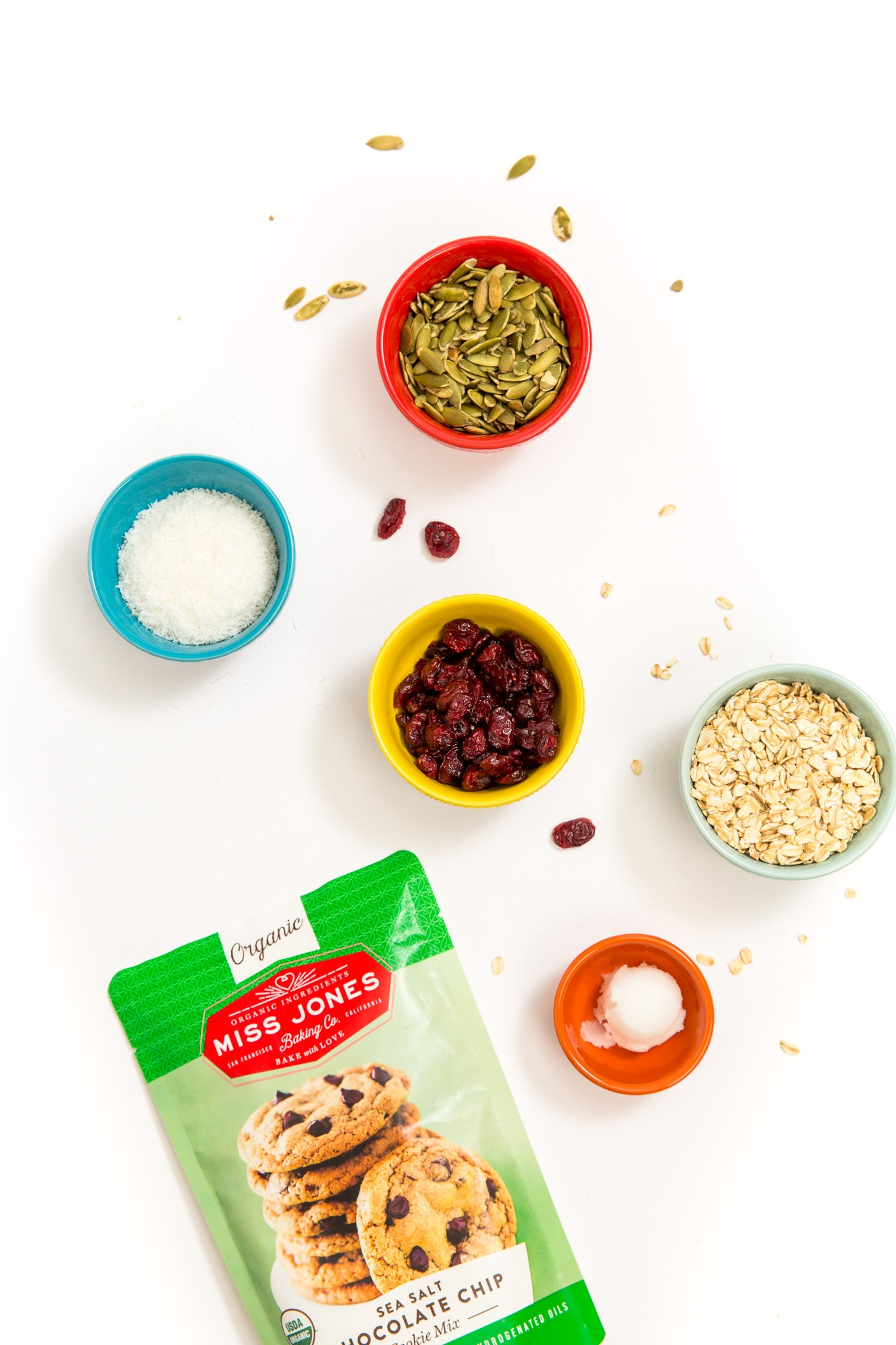 Image of Miss Jones Baking Co Sea Salt Chocolate Chip Cookie Mix next to bowls of coconut flakes, cranberries, pumpkin seeds and oats used for Miss Jones Baking Co Happy Trails Mix Cookie Bites recipe