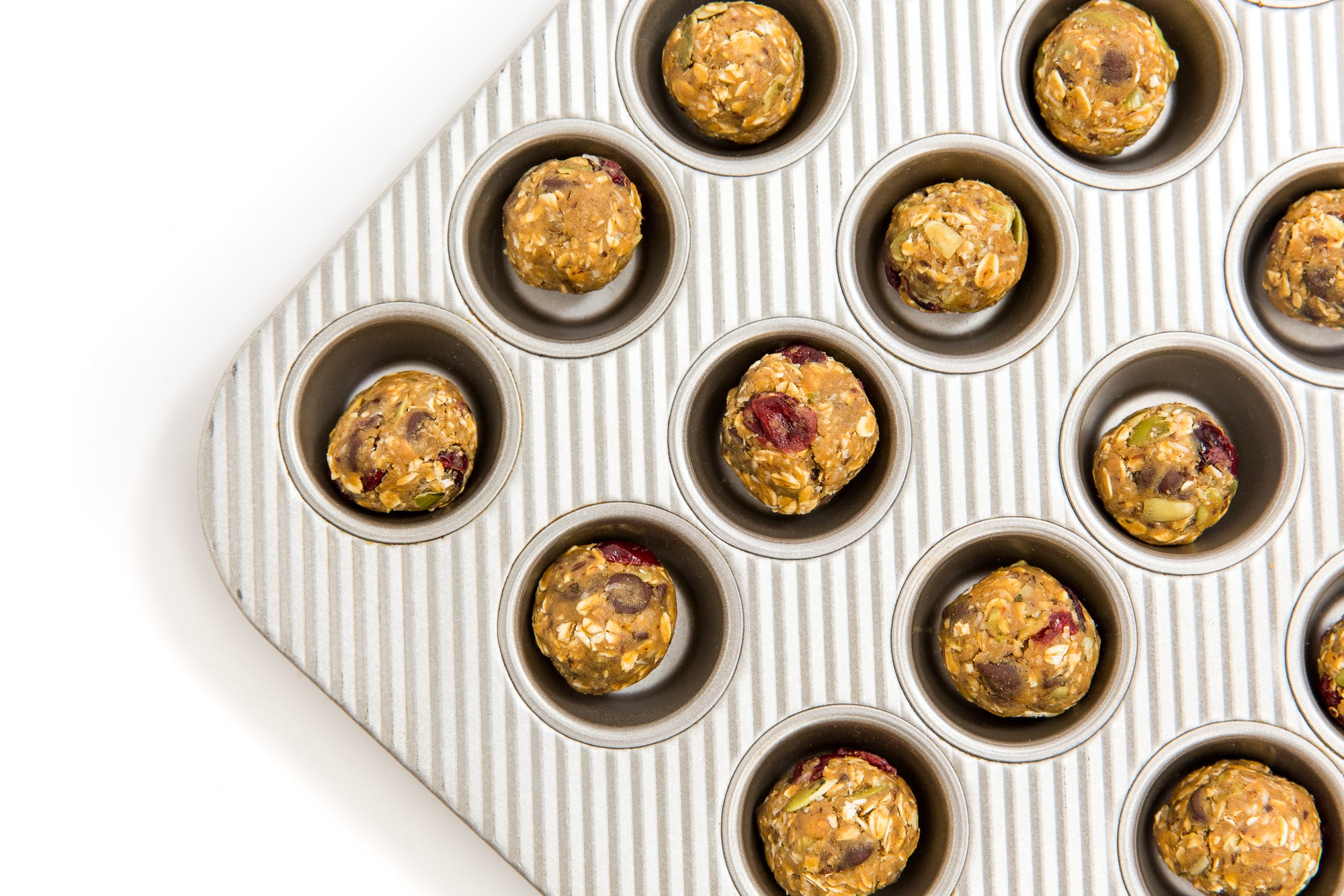 Image of part of a mini cupcake tray with balls of Miss Jones Baking Co Happy Trails Mix Cookie Bites dough