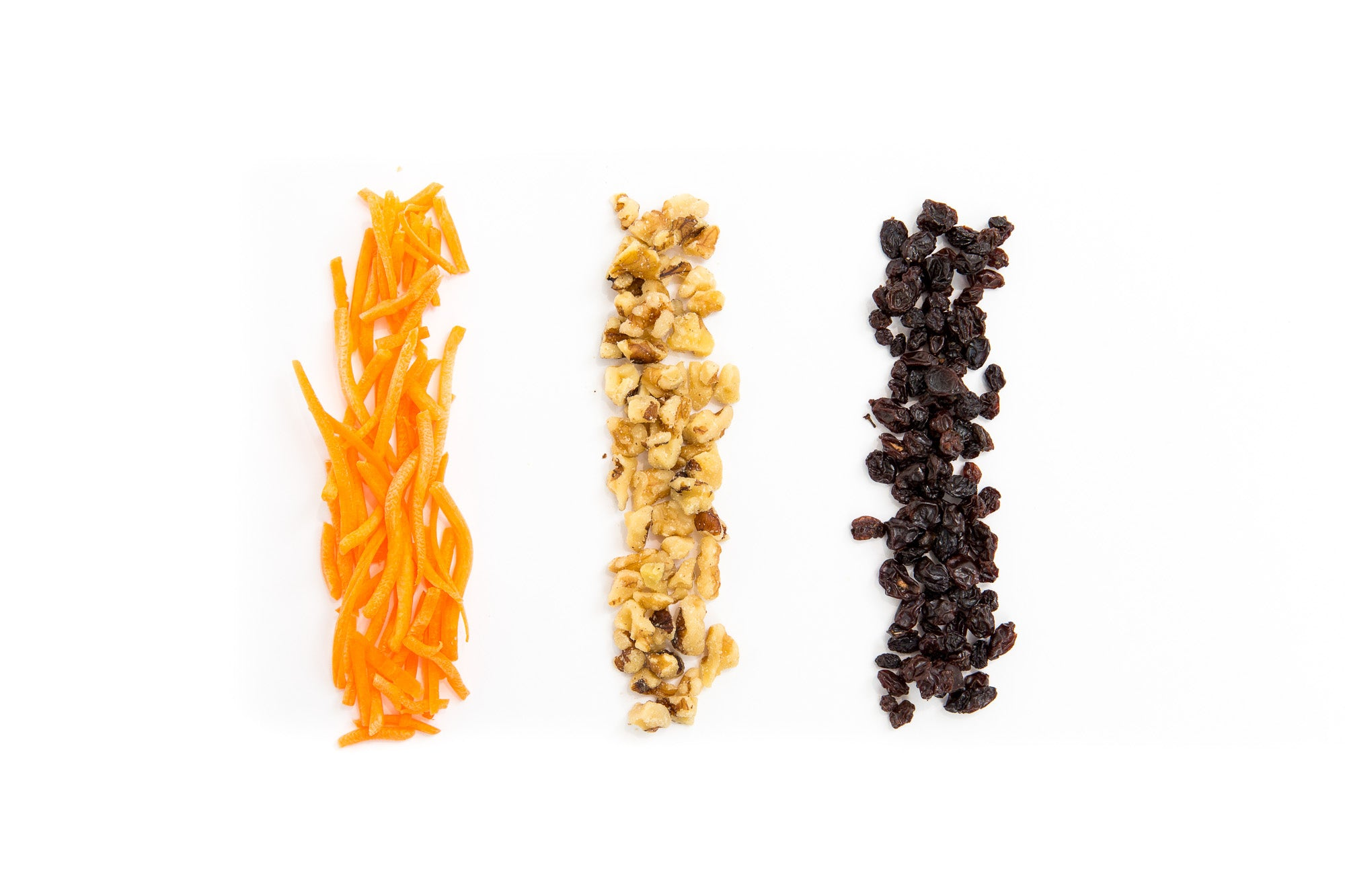 Image of three vertical line piles of carrots, walnuts, and raisins used in Miss Jones Baking Co Carrot Cake Bark