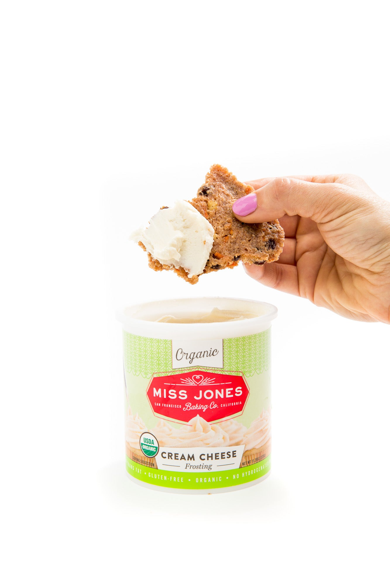 Image of Miss Jones Baking Co Carrot Cake Bark being dipped into a jar of Miss Jones Cream Cheese Frosting