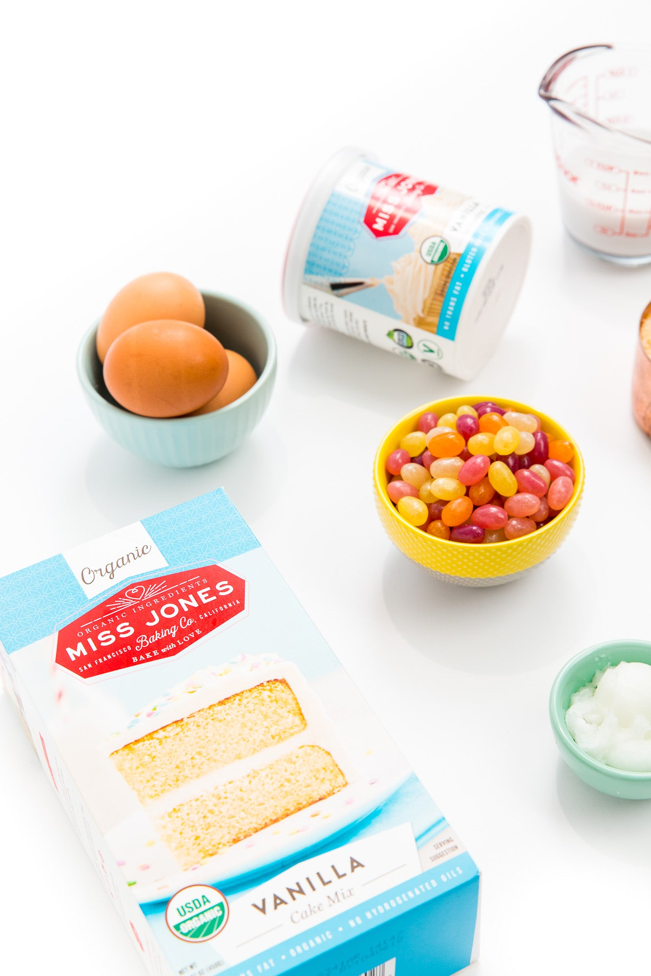 Image of a box of Miss Jones Vanilla Cake Mix, a bowl of three eggs, a bowl of jellybeans, a jar of Miss Jones Vanilla Frosting, and a bowl of coconut oil for Miss Jones Baking Co Toasted Coconut Easter Egg Nest Cupcakes recipe