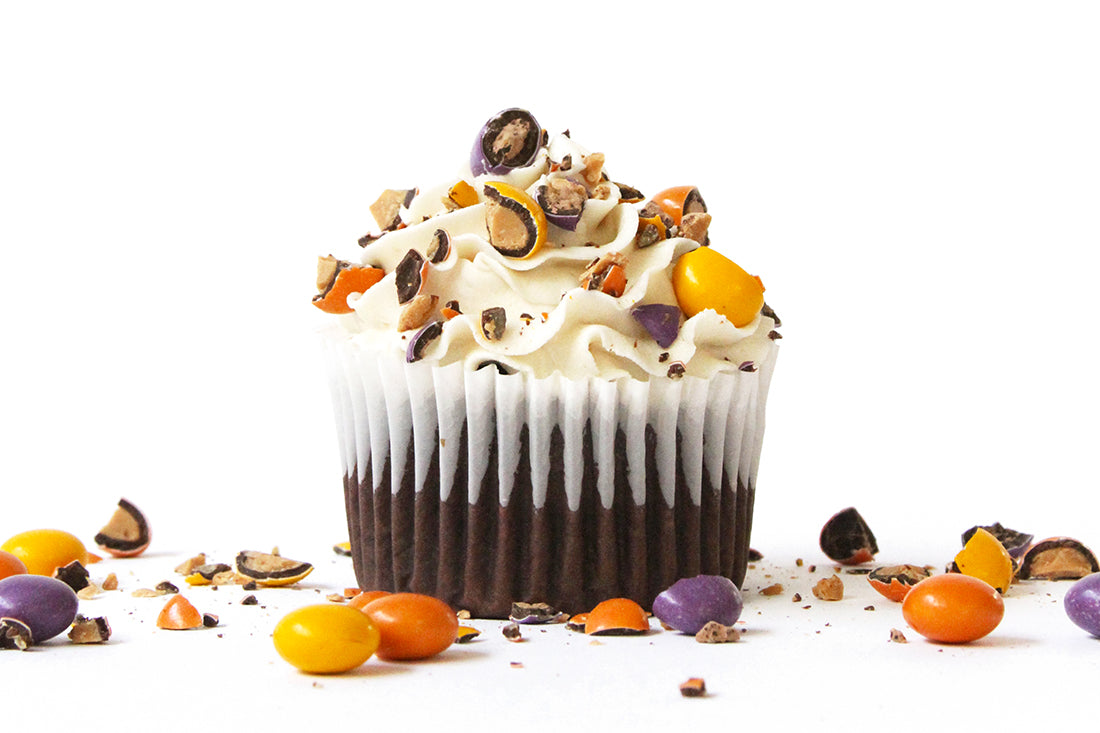 Image of the side of a Miss Jones Baking Co Spooky Secret Cupcake surrounded by crushed Little Secrets Peanut Butter Dark Chocolate Candies