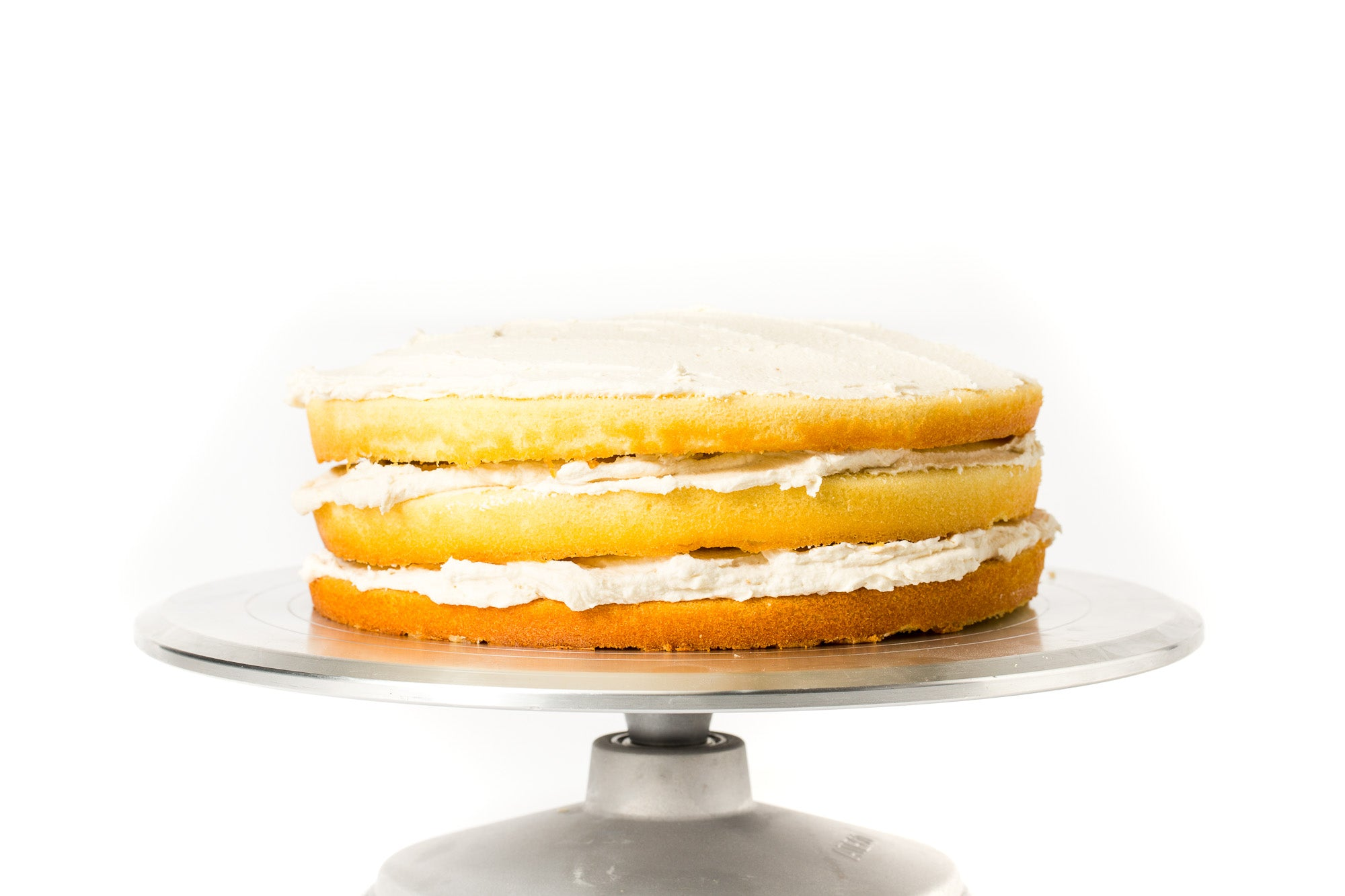 Image of three layers of stacked cakes and frosting for Miss Jones Baking Co Floral Bloom Layer Cake on a cake stand