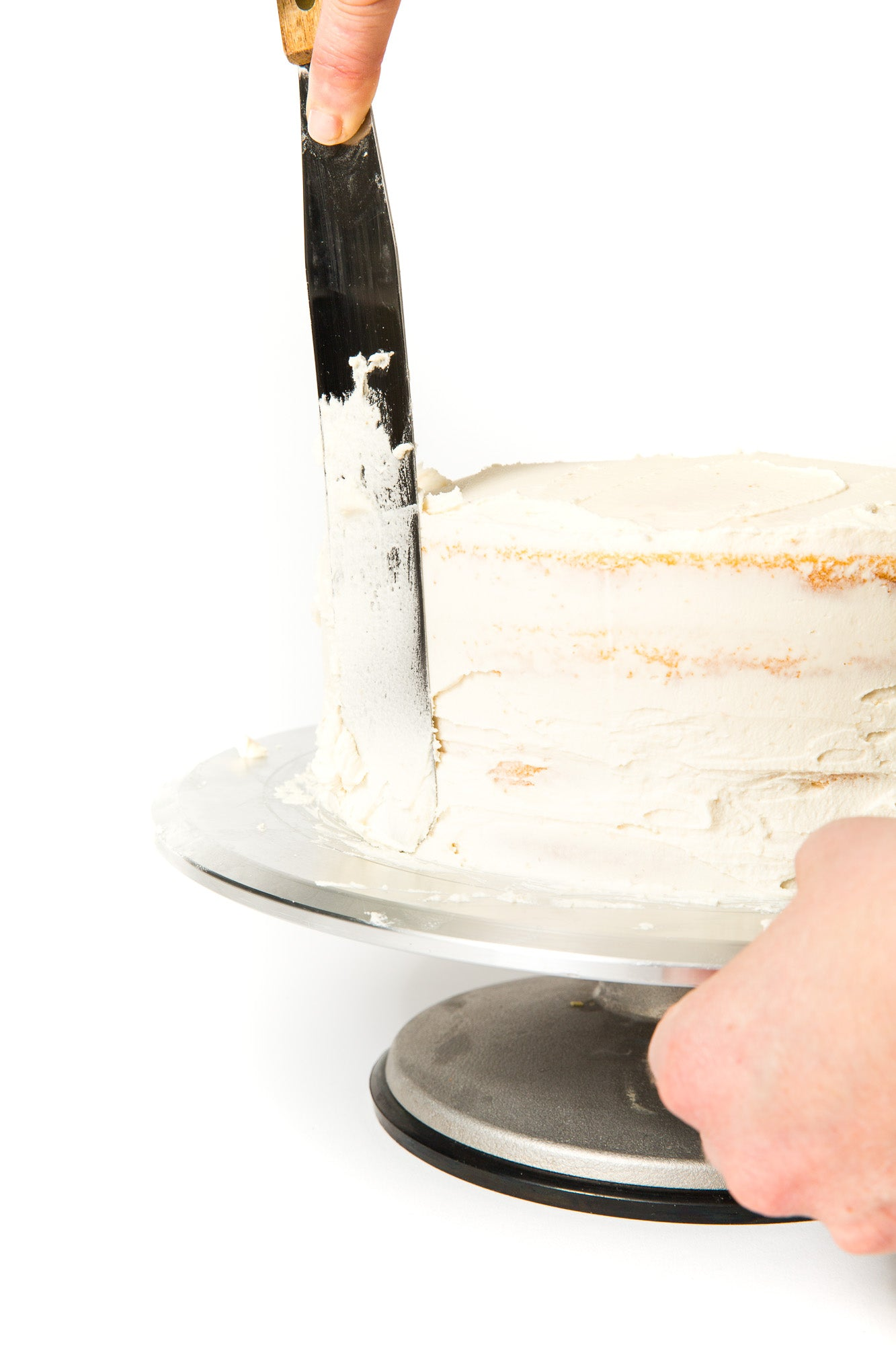 Image of part of Miss Jones Baking Co Floral Bloom Layer Cake being frosted on a cake stand
