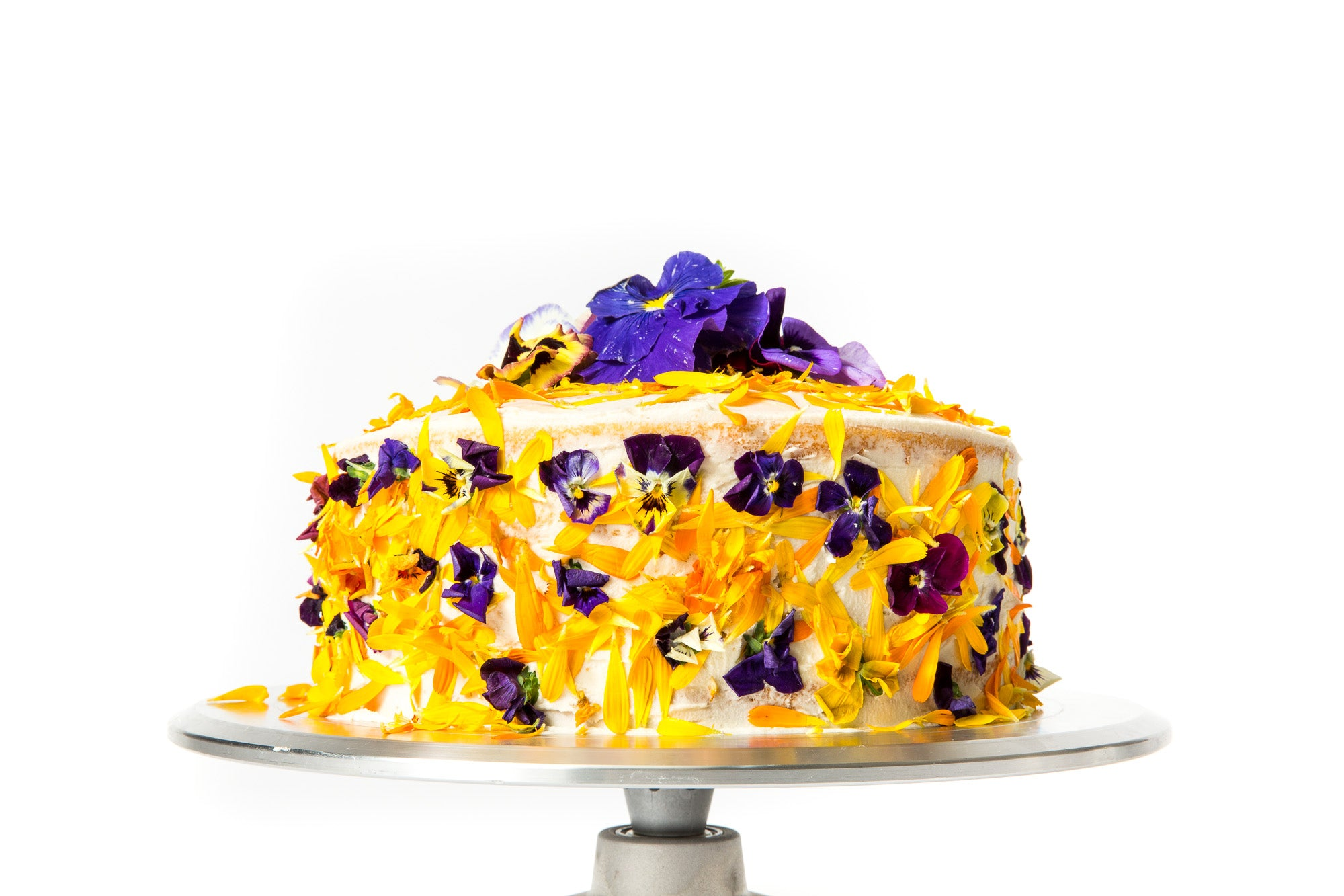 Image of the side of Miss Jones Baking Co Floral Bloom Layer Cake on a cake stand