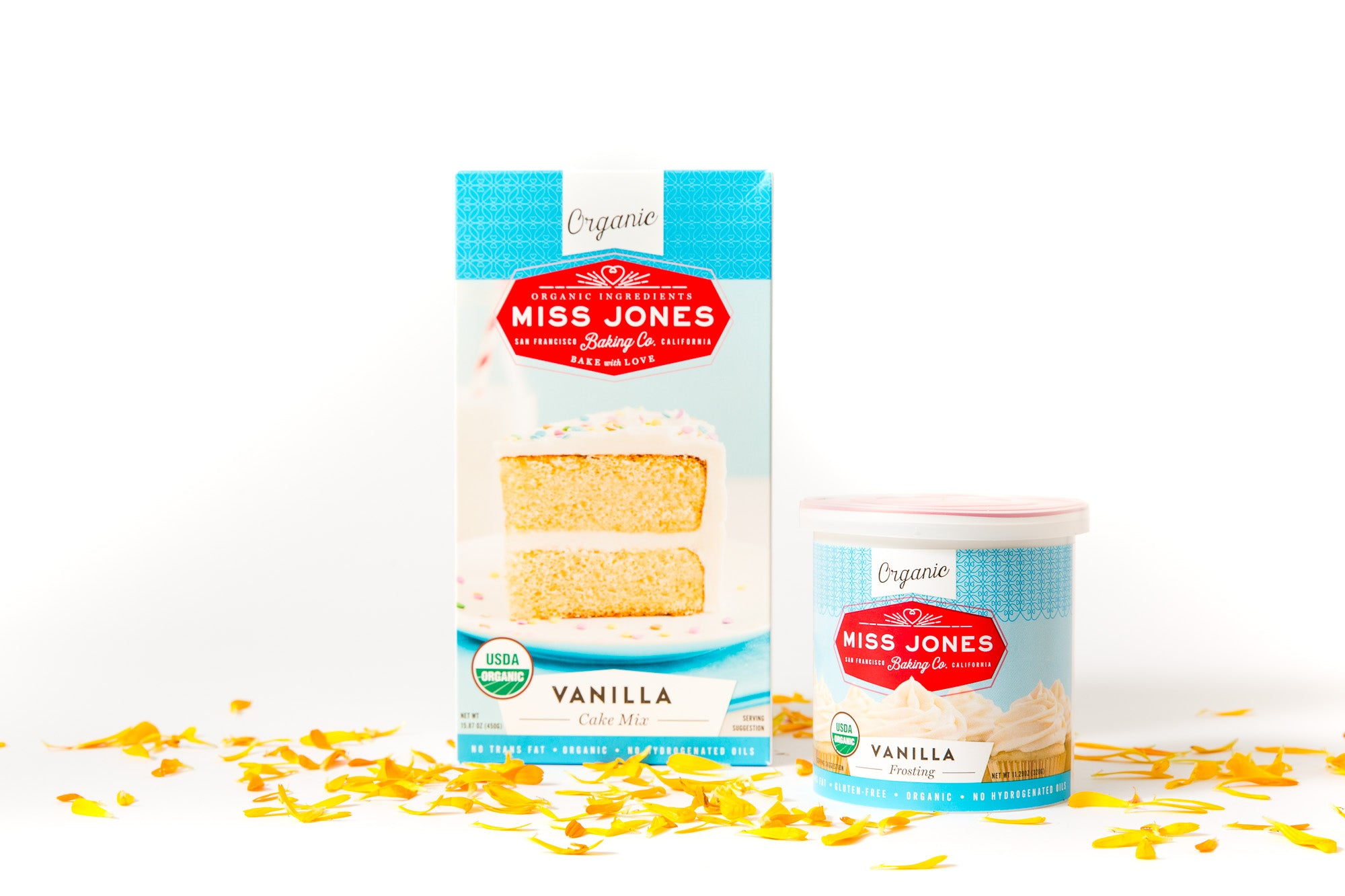 Image of a box of Miss Jones Vanilla Cake Mix and a jar of Miss Jones Vanilla Frosting surrounded by yellow flower petals for Miss Jones Baking Co Floral Bloom Layer Cake