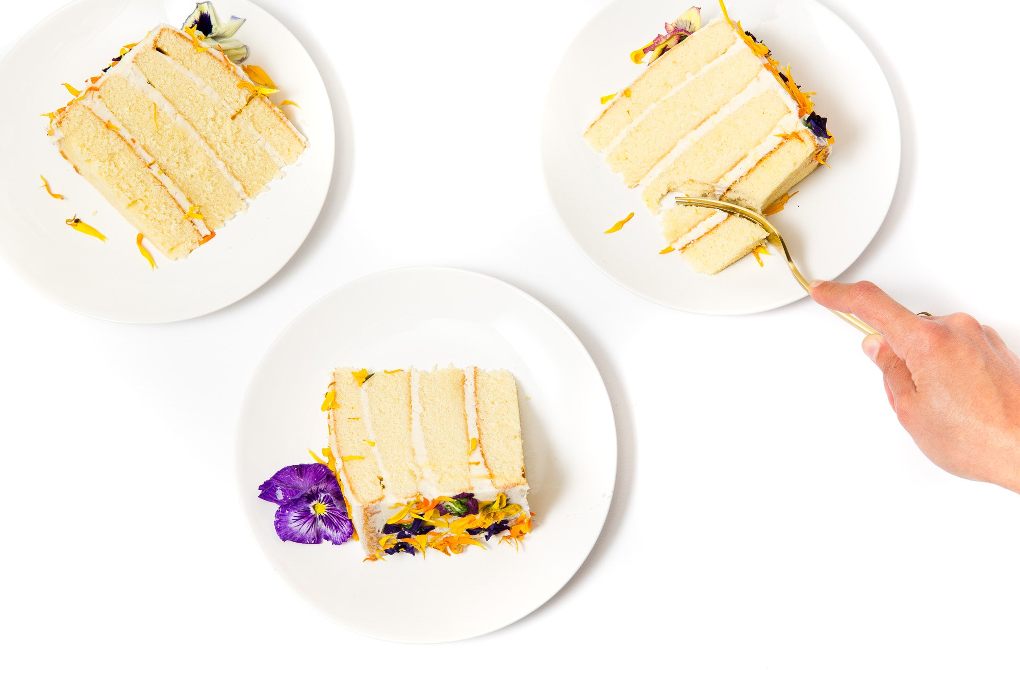 Image from above of three pieces of Miss Jones Baking Co Floral Bloom Layer Cake on plates