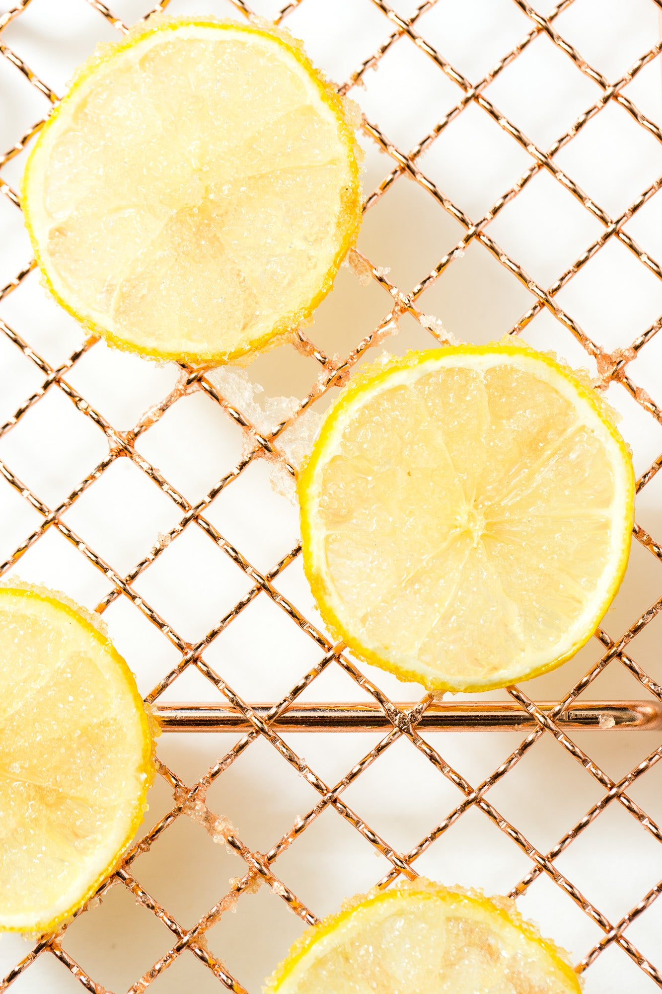 A close up image of thinly sliced candied lemons on a baking rack for Miss Jones Baking Co Lemonade Donuts