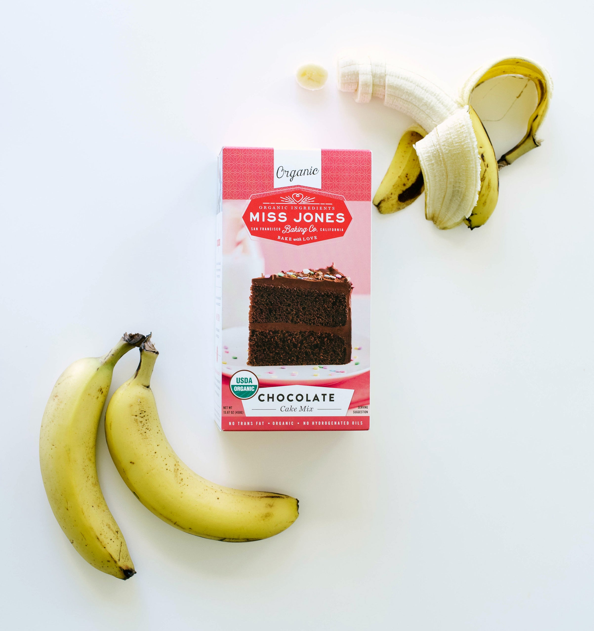 A box of Miss Jones Chocolate Cake Mix surrounded by three bananas used for Miss Jones Baking Co Chocolate Cake Batter Peanut Butter Nice Cream recipe