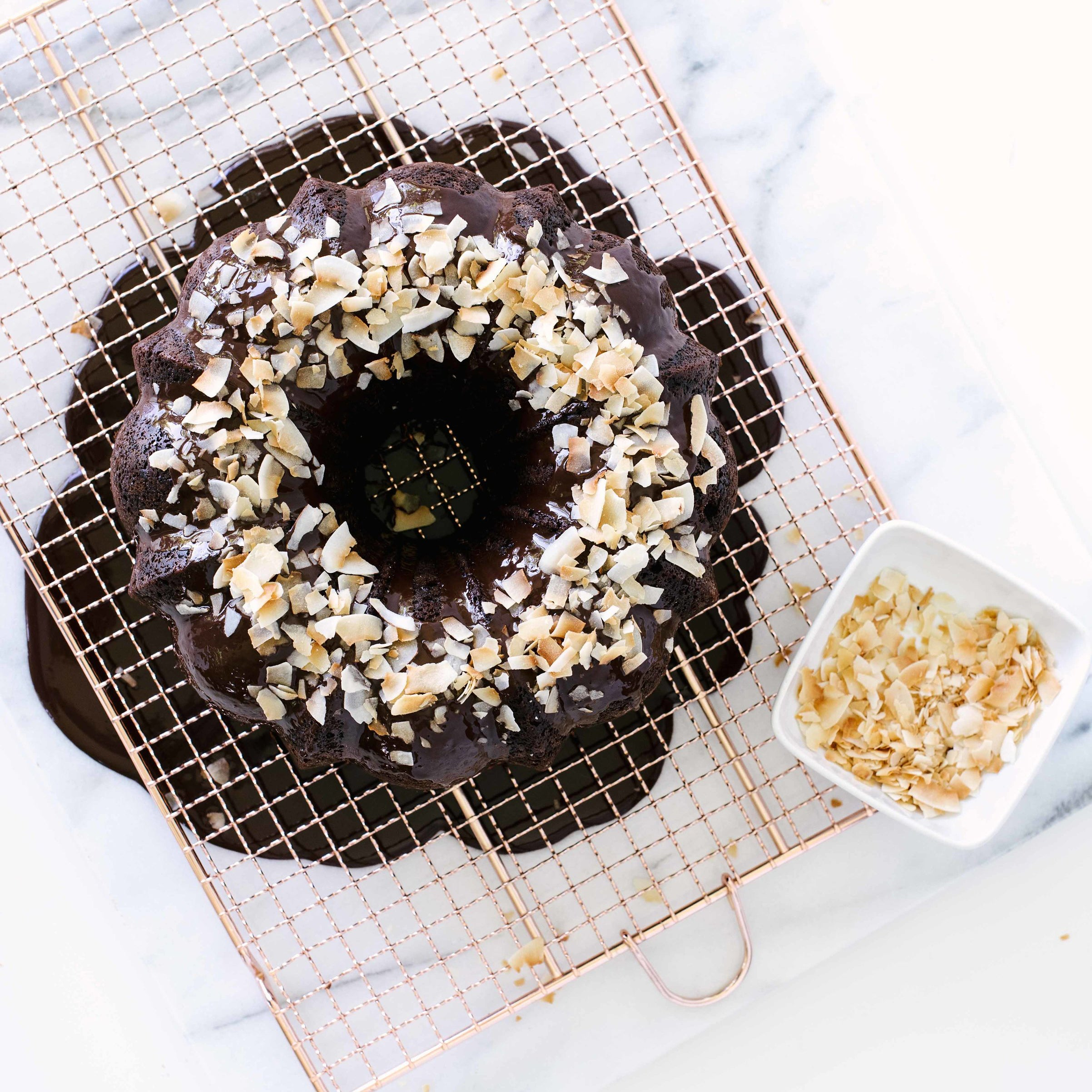 Top of Miss Jones Dark Chocolate Coconut Bundt Cake on a baking sheet with toasted coconut flakes on the cake and in a bowl to the side
