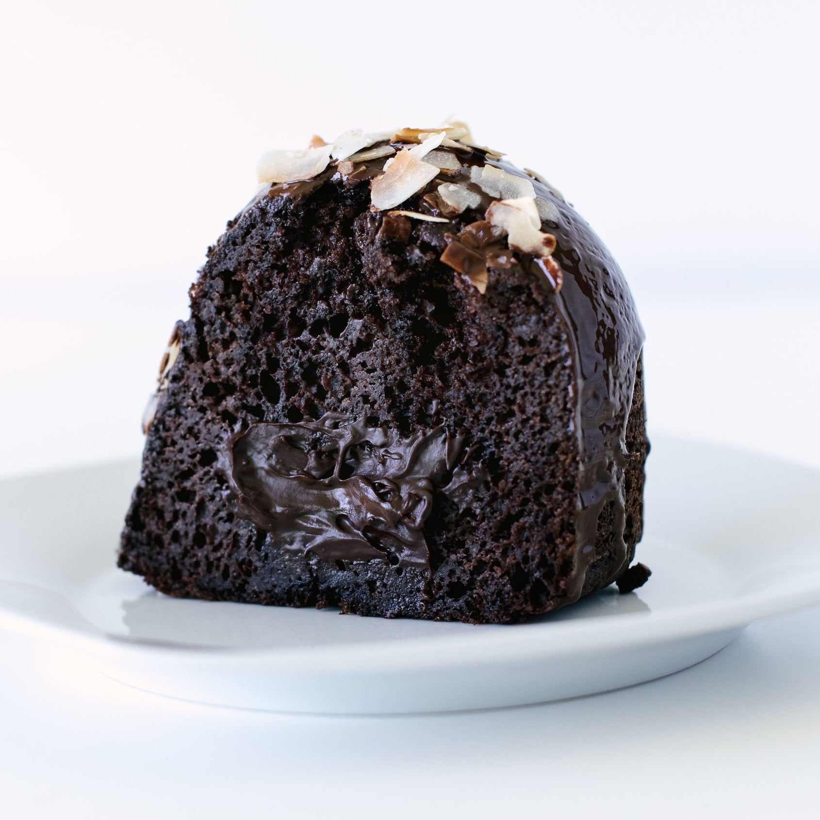 Close up of inside of a slice of Miss Jones Baking Co Dark Chocolate Coconut Bundt Cake on a white plate