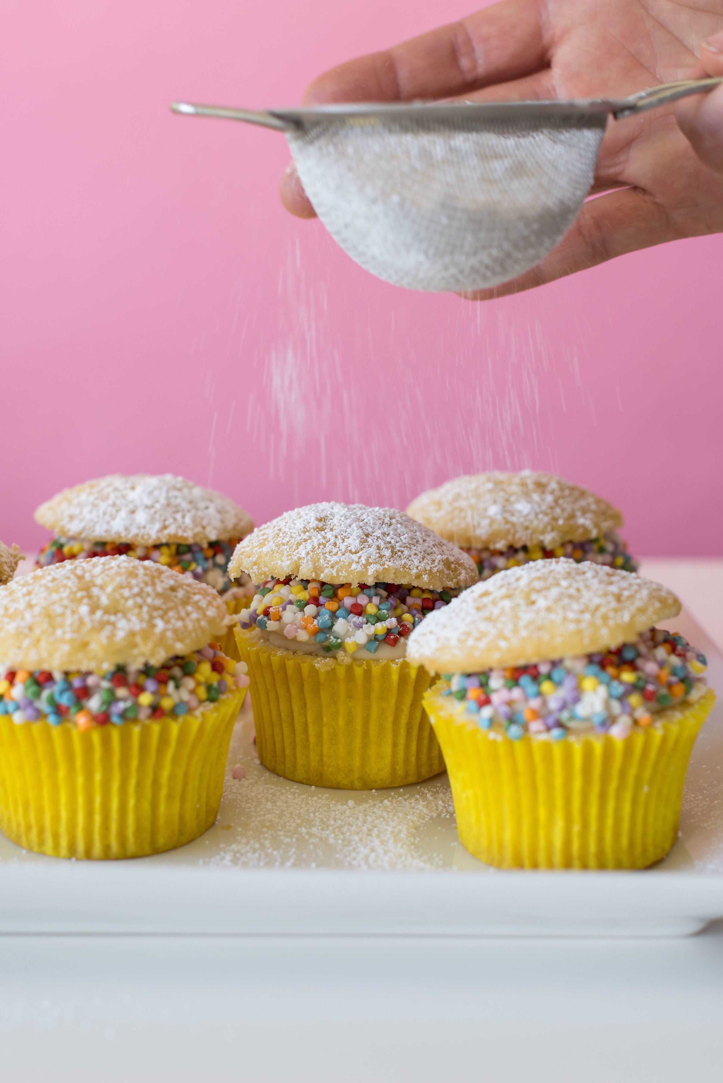 Image of side of five Miss Jones Baking Co Confetti Pop Cream Puff Cupcakes being sprinkled with powdered sugar