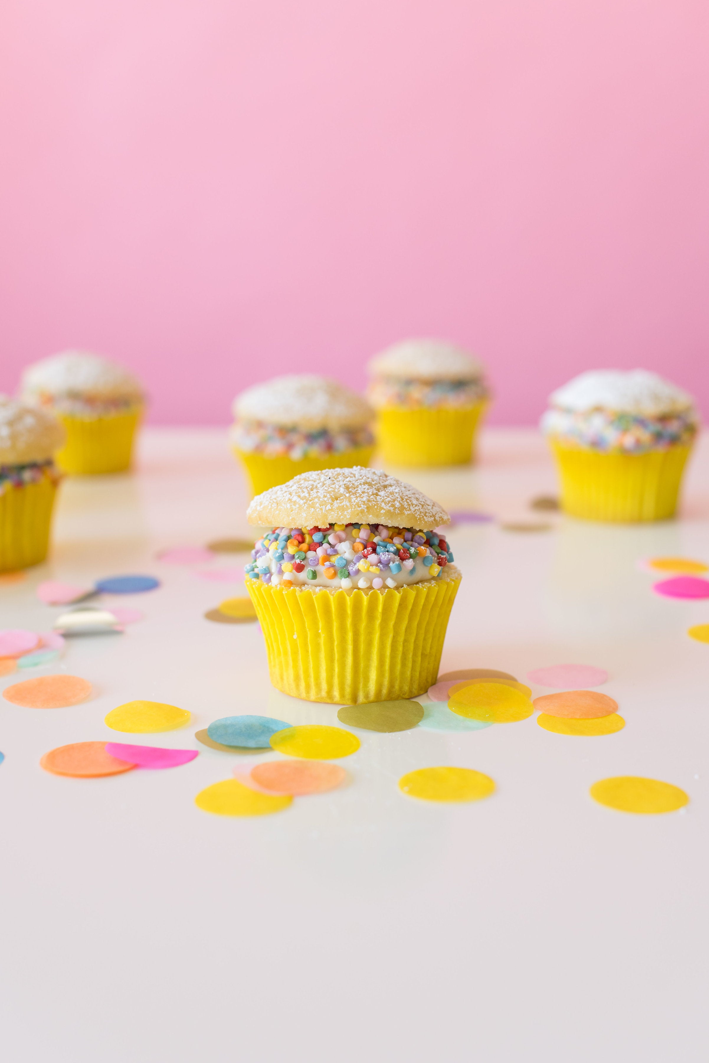 Image of side of six Miss Jones Baking Co Confetti Pop Cream Puff Cupcakes surrounded by confetti