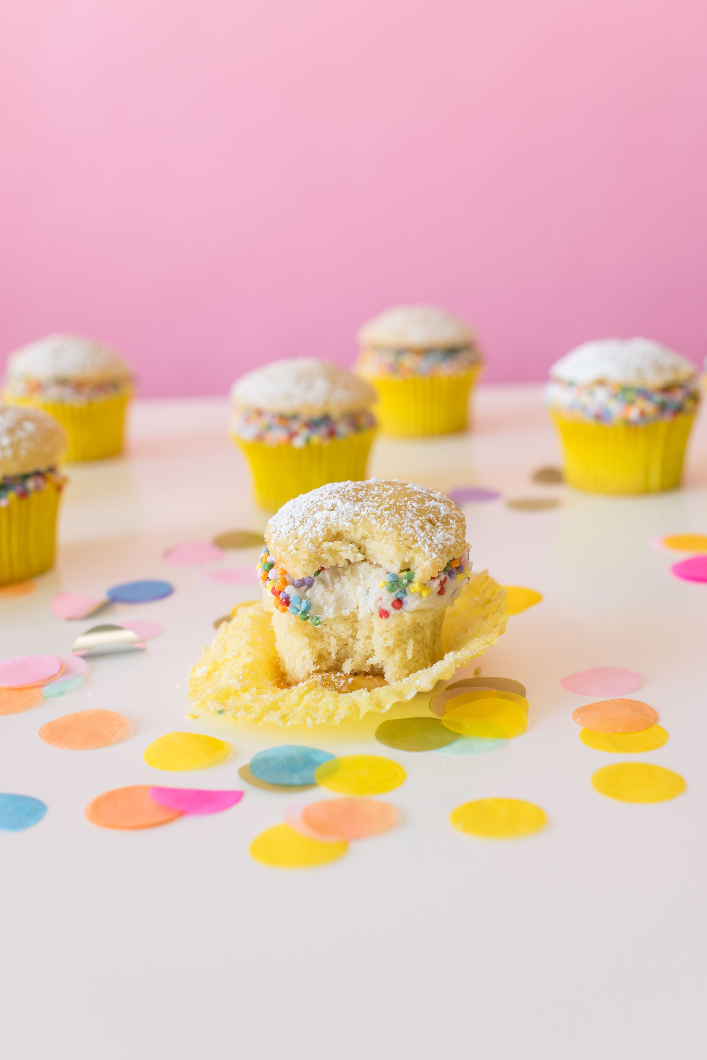 Image of side of six Miss Jones Baking Co Confetti Pop Cream Puff Cupcakes with a bite taken out of middle cupcake