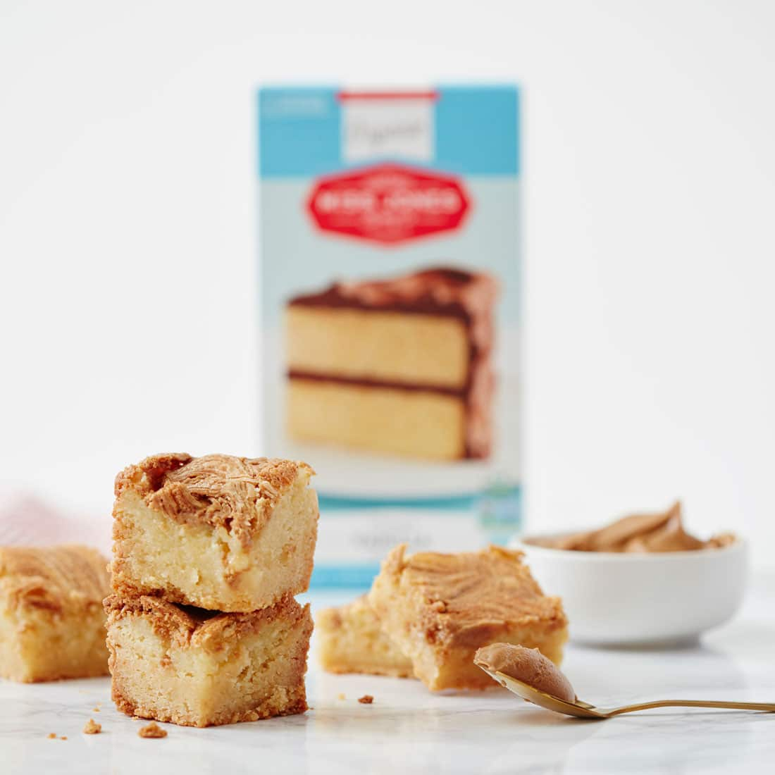 A stack of a few of Miss Jones One-Bowl Cookie Butter Gooey Butter Bars in front of a box of Miss Jones Organic Vanilla Cake Mix