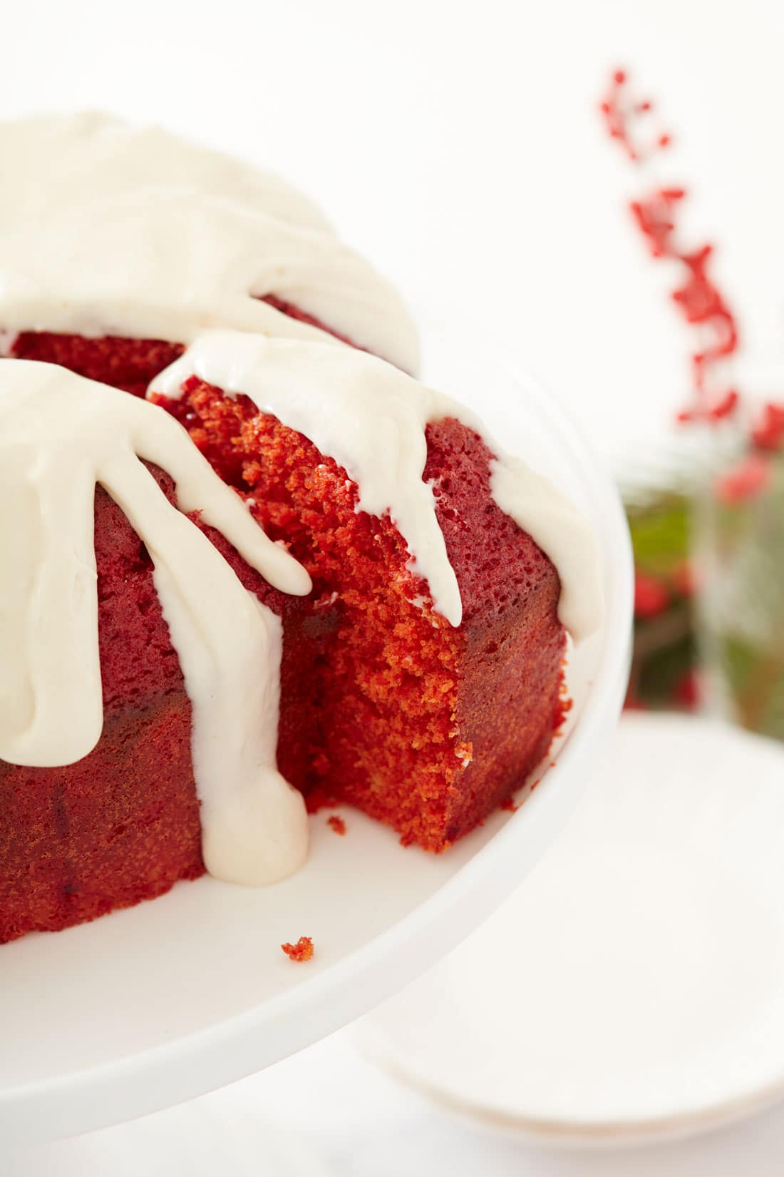 Closeup Image of Miss Jones Baking Co's Red Velvet Bundt Cake and Cream Cheese Glaze with a slice being cut