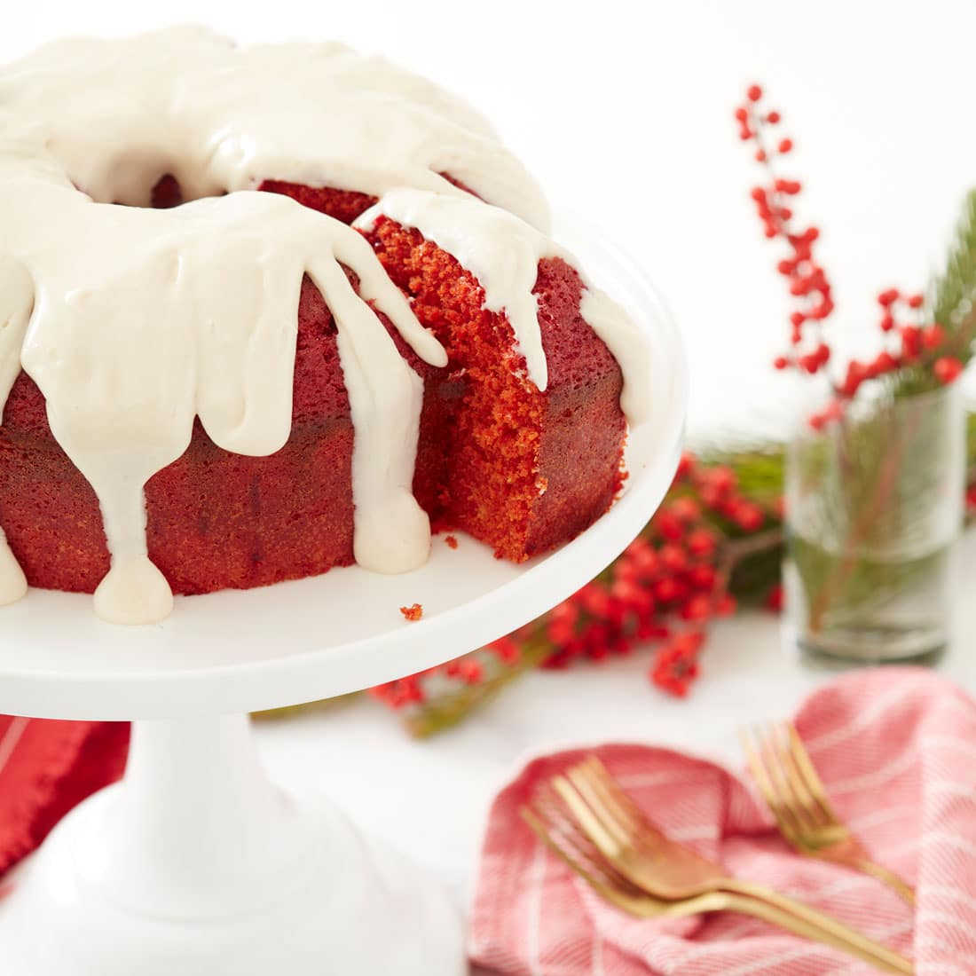 Side image of Miss Jones Baking Co's Red Velvet Bundt Cake and Cream Cheese Glaze with a slice being cut