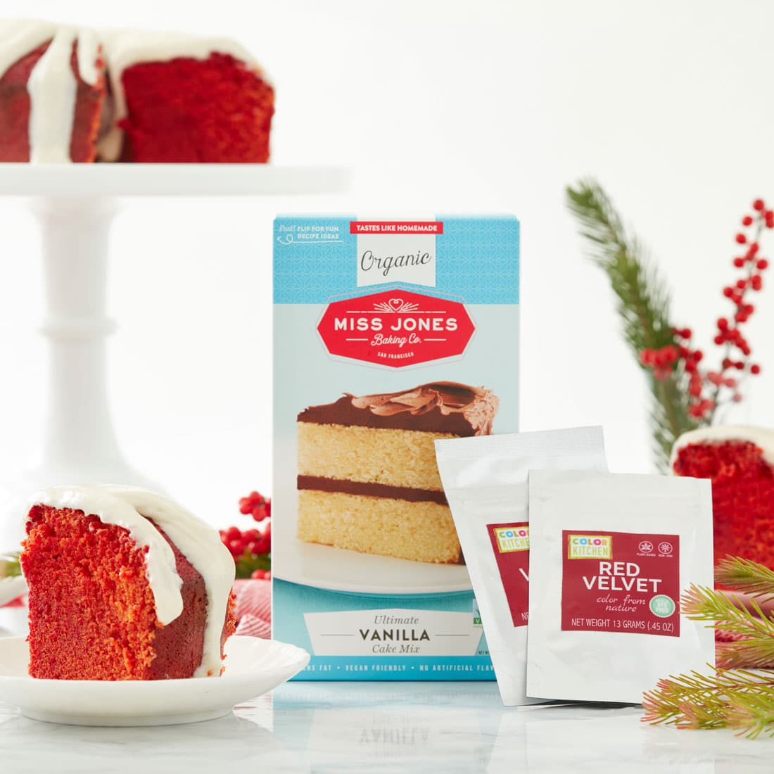 Image of Miss Jones Baking Co's Red Velvet Bundt Cake and Cream Cheese Glaze slice and Miss Jones Baking Co Vanilla Organic Cake Mix in the background