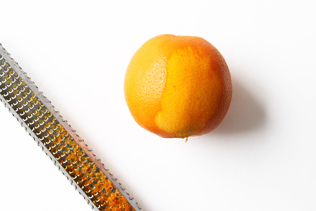 Image of a zested orange next to a zester with orange zest for Miss Jones Baking Co Marmalade Madeleines