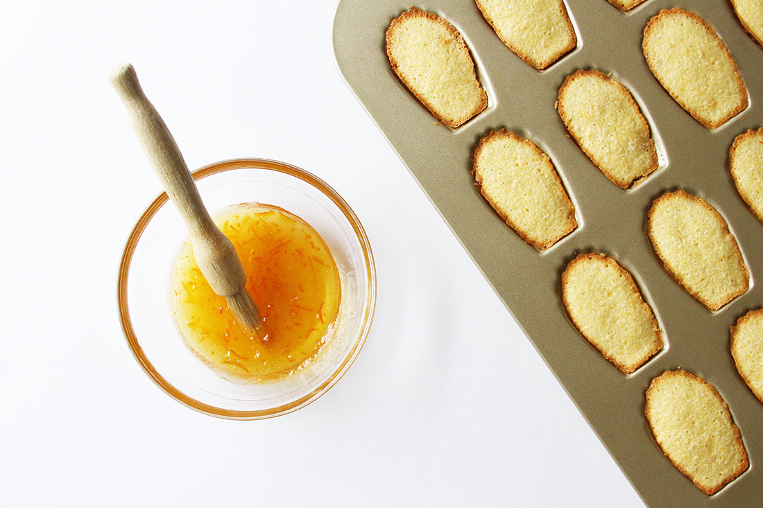 Image of part of a tray of Madeleines in a baking mold next to a bowl of marmalade for Miss Jones Baking Co Marmalade Madeleines