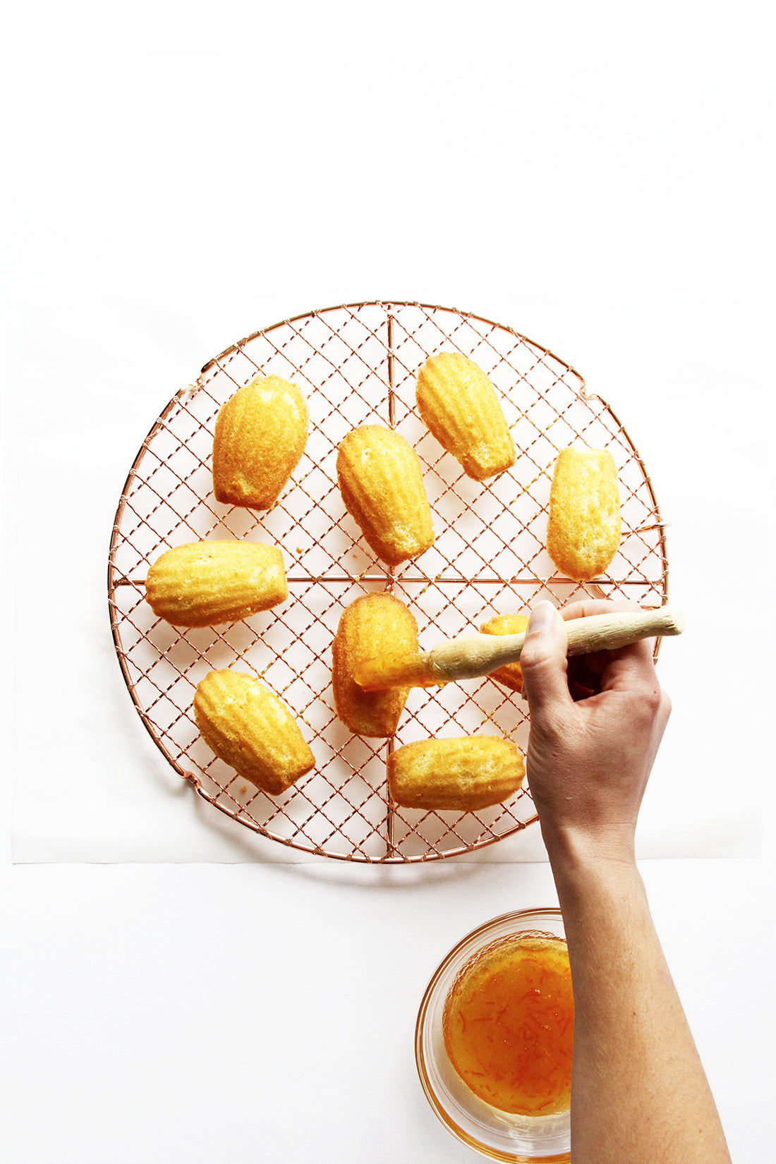 Image of nine Miss Jones Baking Co Marmalade Madeleines on a baking rack being glazed with orange marmalade by a hand