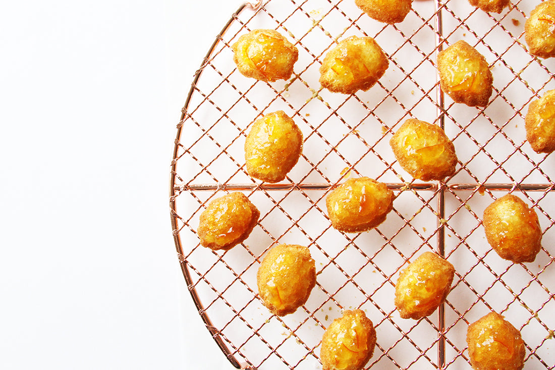 Close up image of Miss Jones Baking Co Marmalade Madeleines on a baking rack
