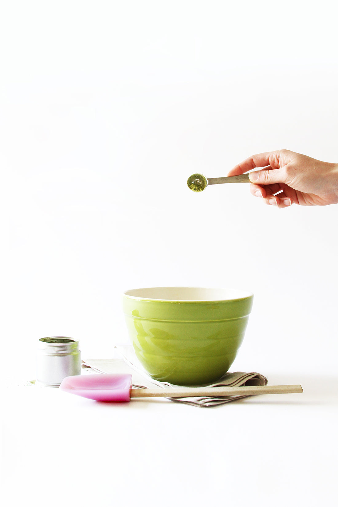 Image from the side of a spoon of matcha poured into a green mixing bowl next to a jar of powdered matcha and a purple spatula for Miss Jones Baking Co Matcha Tea Cakes