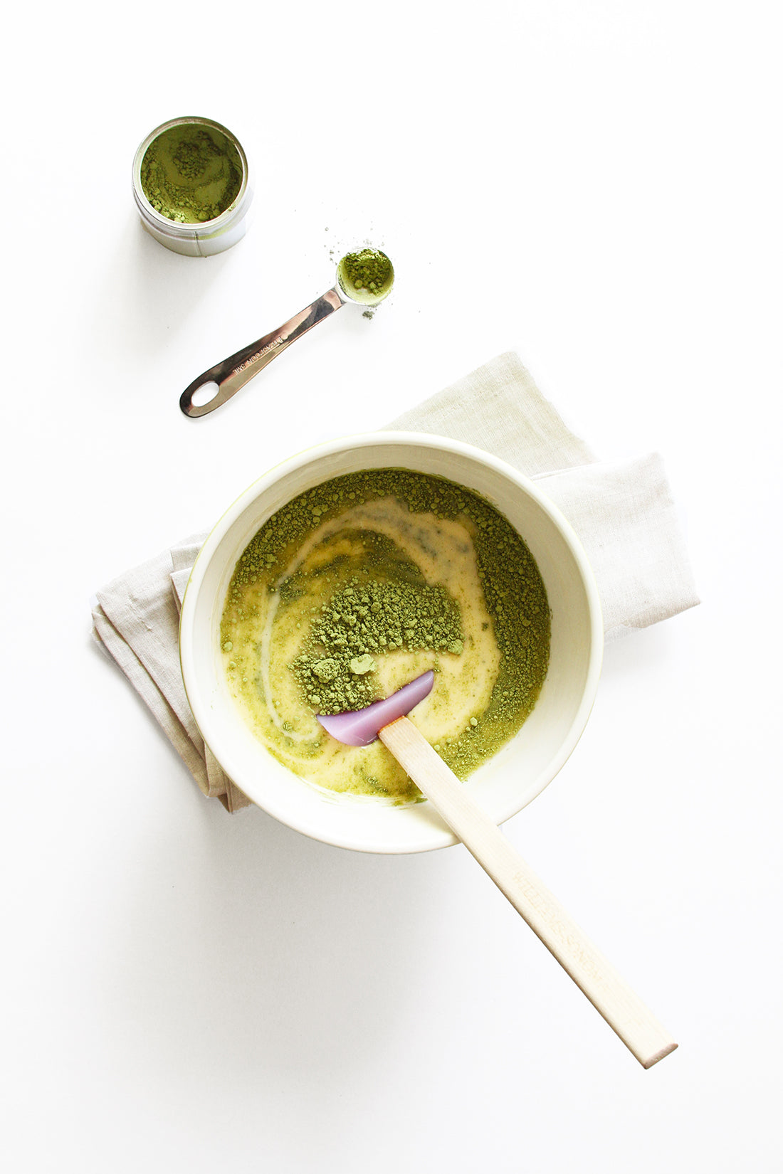 Image from above of matcha powder mixing into the batter of Miss Jones Baking Co Matcha Tea Cakes