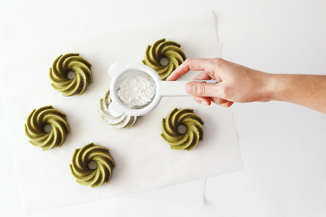 Image from above of a hand putting powdered sugar on top of six Miss Jones Baking Co Matcha Tea Cakes