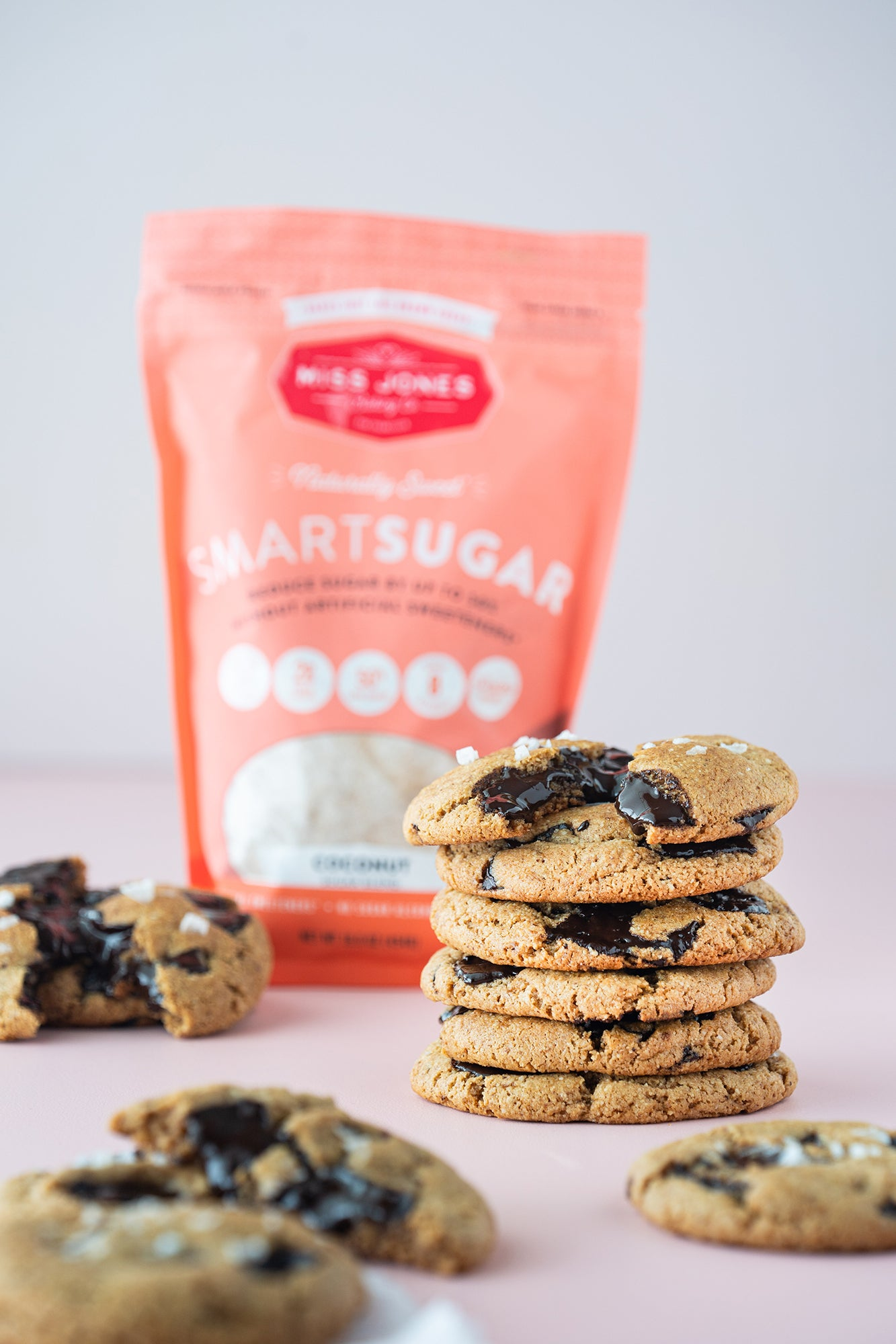 Image of stacked Miss Jones Baking Co Paleo Chocolate Chip Cookies in front of a bag of SmartSugar Coconut Sugar Blend