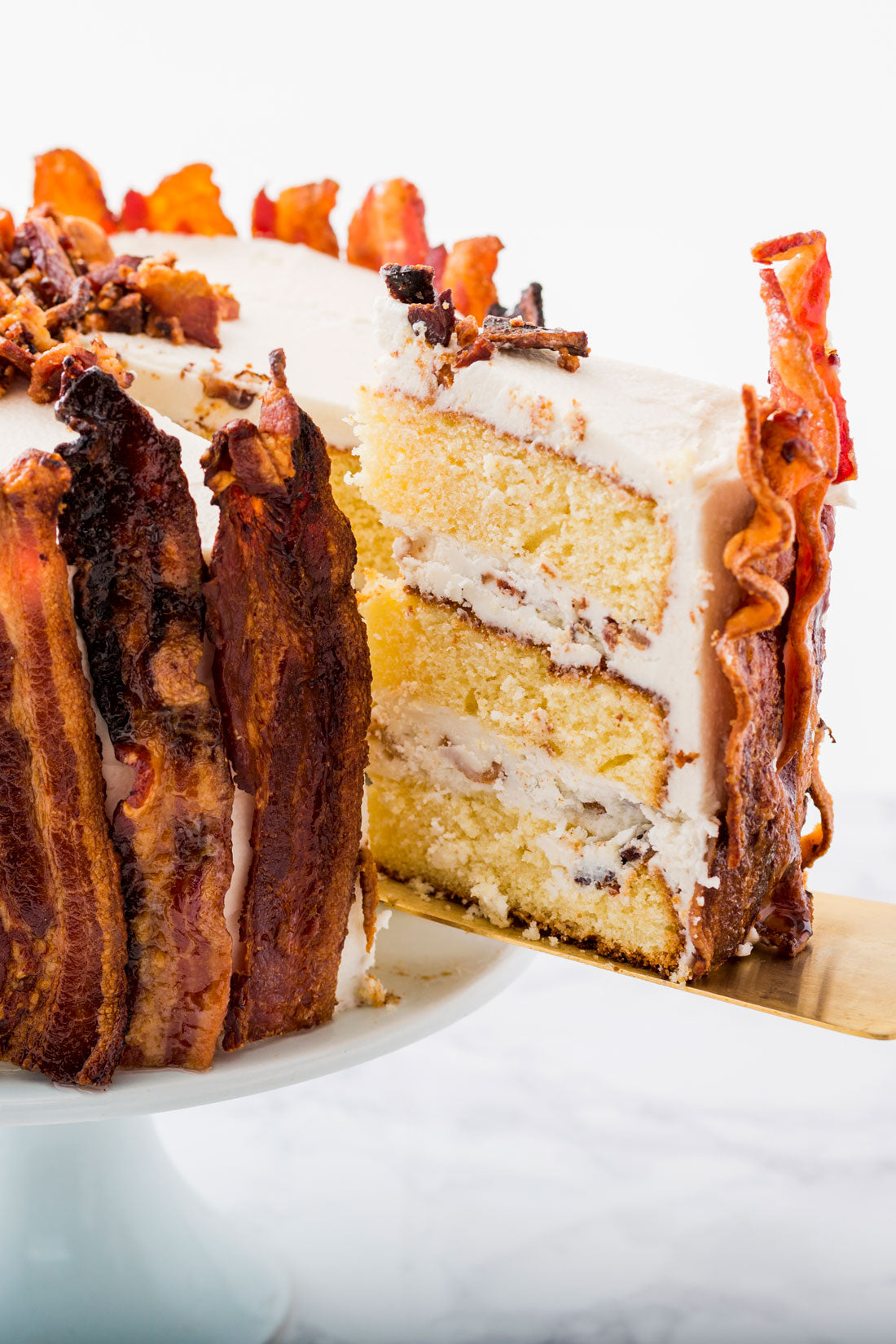 A close up image of a slice being removed from Miss Jones Baking Co Epic Father's Day 3-Layer Bacon and Beer Cake