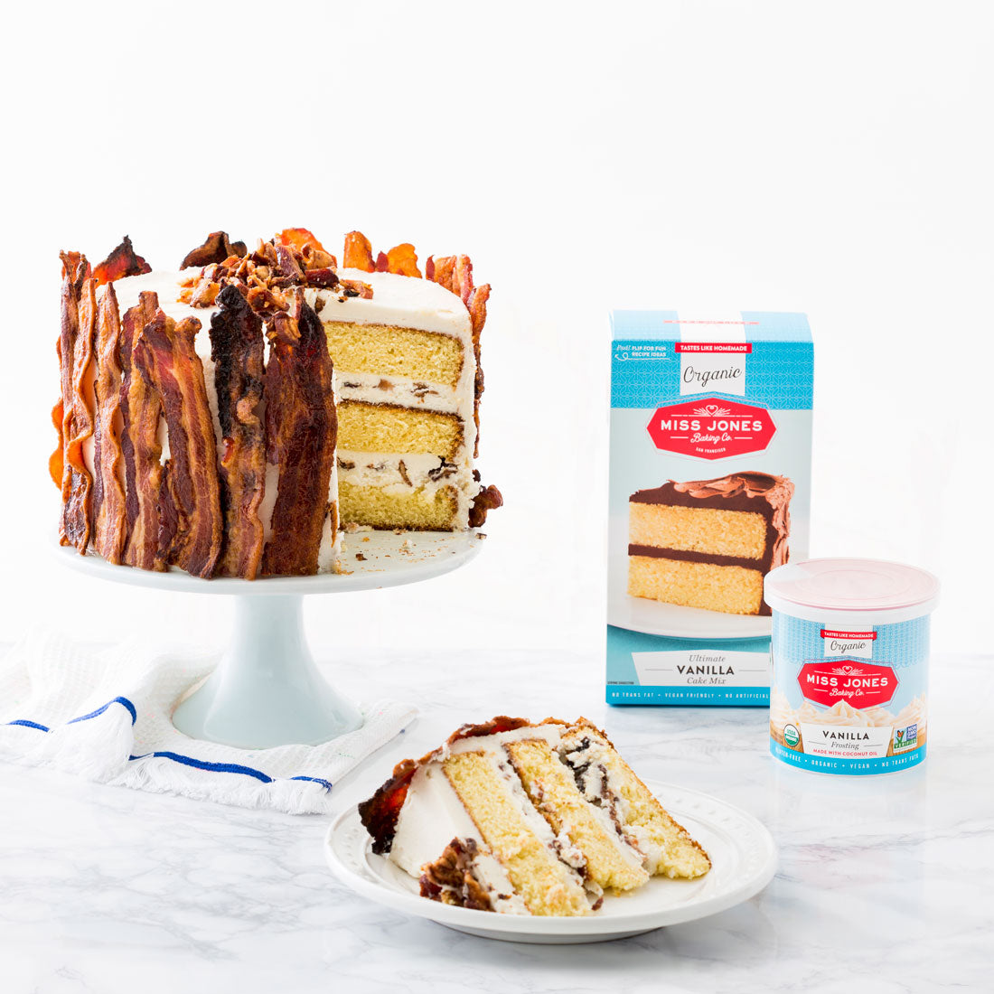 Image of side of Miss Jones Baking Co Epic Father's Day 3-Layer Bacon and Beer Cake on a cake stand with a slice on a plate below, next to a box of Miss Jones Vanilla Cake Mix and a jar of Miss Jones Vanilla Frosting