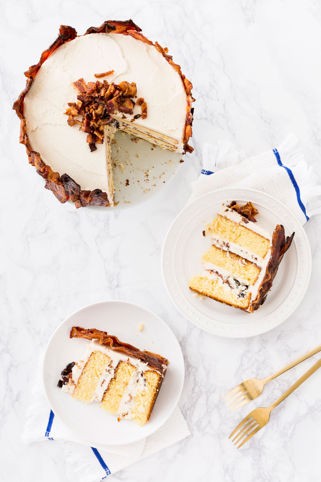 Image of the top of Miss Jones Baking Co Epic Father's Day 3-Layer Bacon and Beer Cake with two slices removed and on plates next to the cake