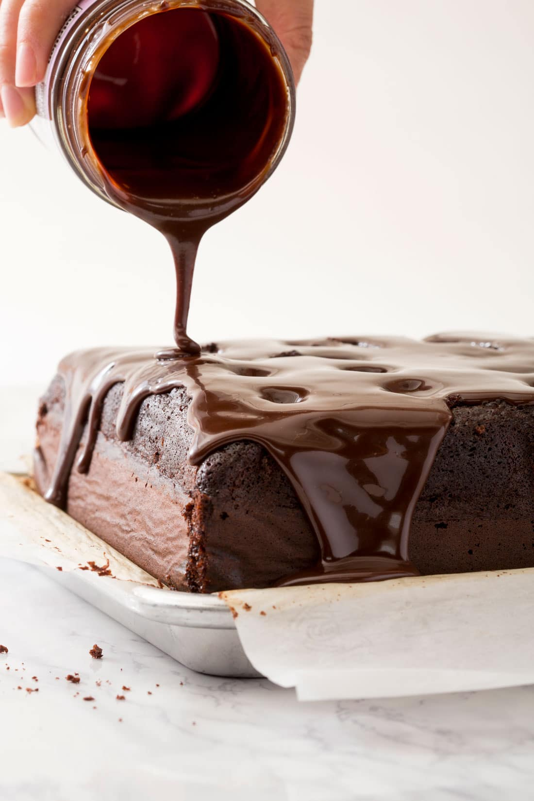 A jar of hot fudge being poured on the top of Miss Jones Chocolate S'mores Poke Cake