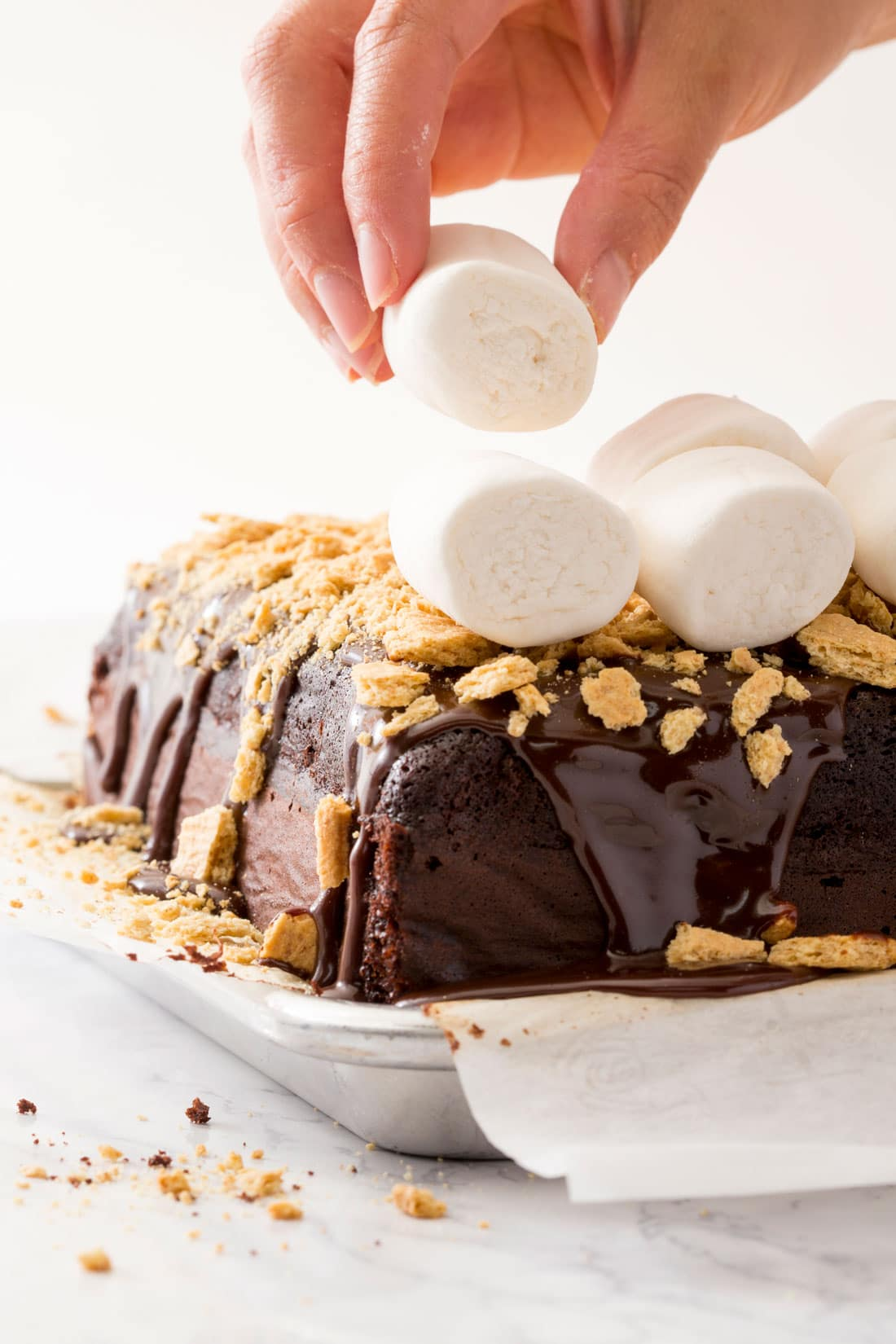 A hand placing marshmallows on top of Miss Jones Chocolate S'mores Poke Cake